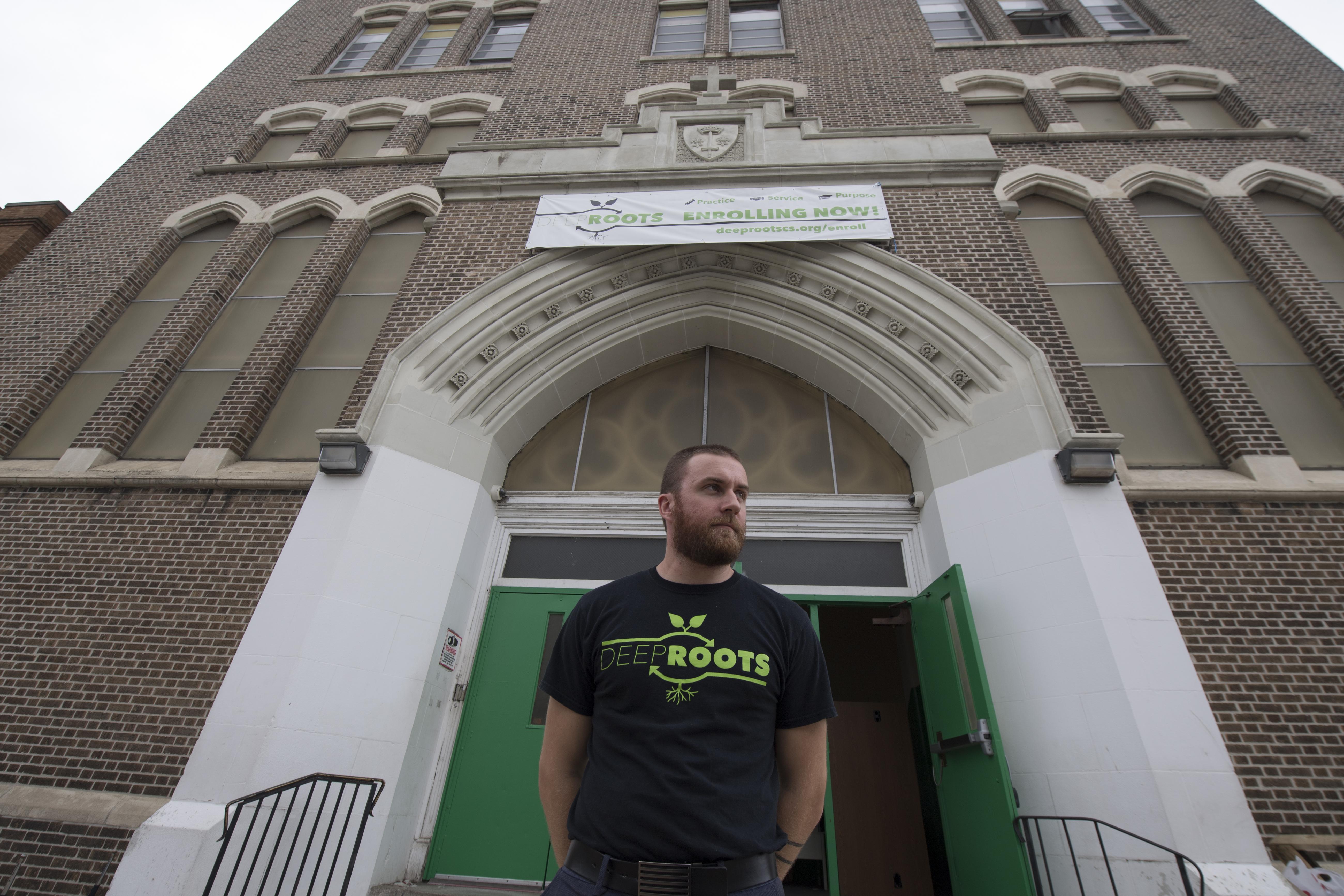 G. Logan Blyler, school leader, in front of Deep Roots Charter School