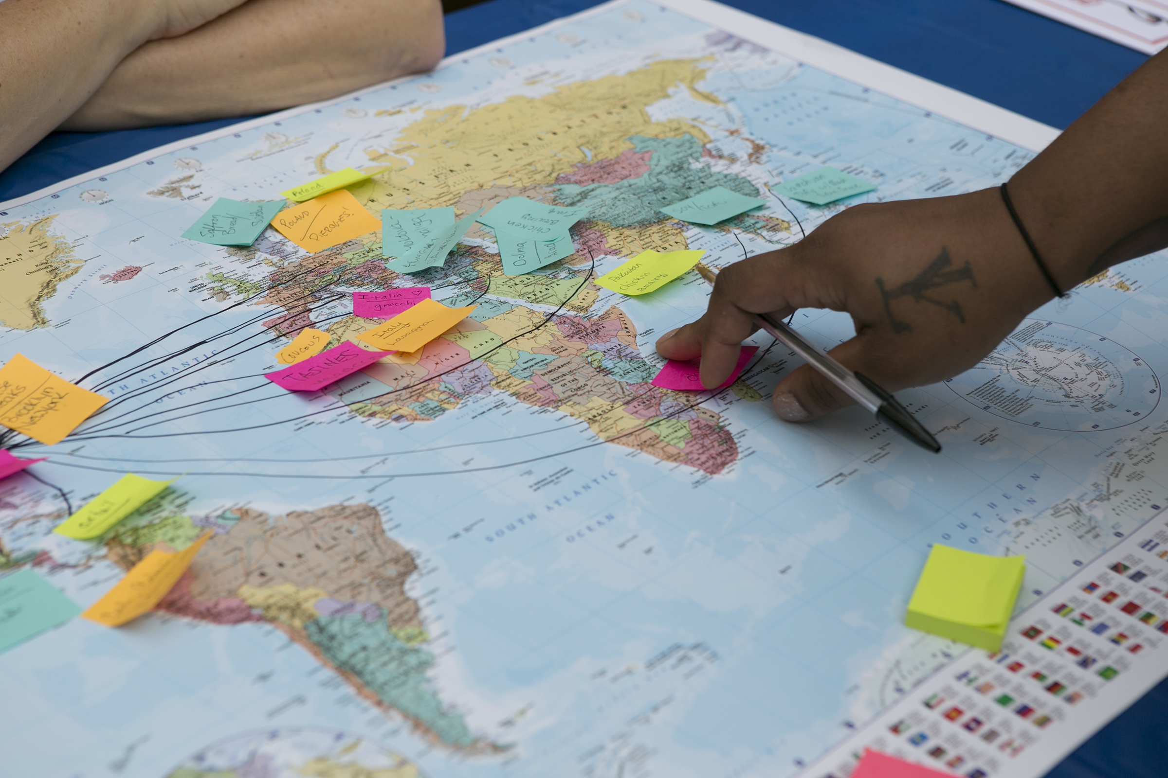 """Brittnay Robinson, 29, places a post it note with the name of her favorite food on the world """"food map"""" at the World Refugee Day celebration at Philadelphia City Hall in June."""