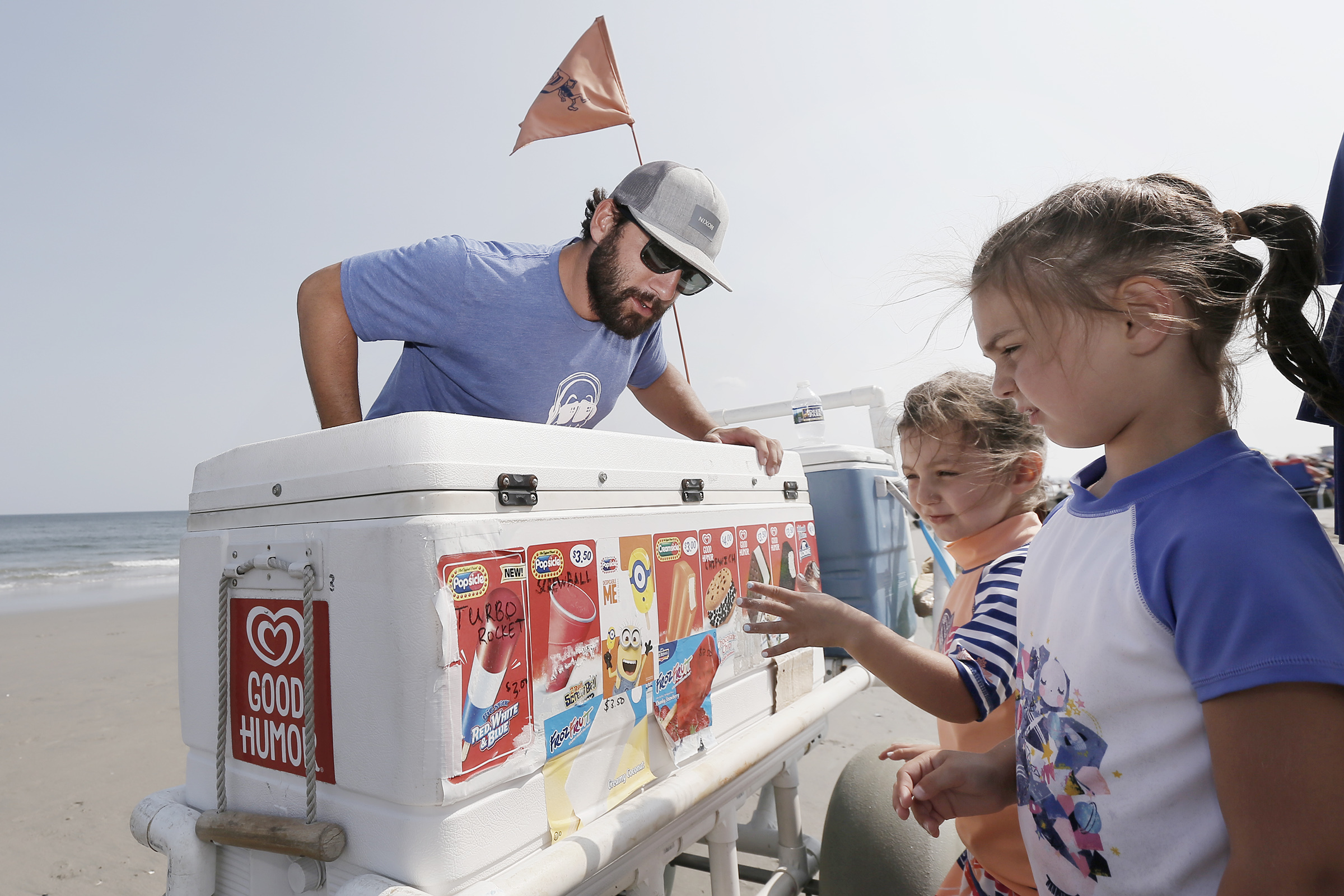 Fudgie Wudgie Ryan McNesby helps Madeline Colella, 5, (middle) and her sister Cecelia Colella, 3, make their selections.