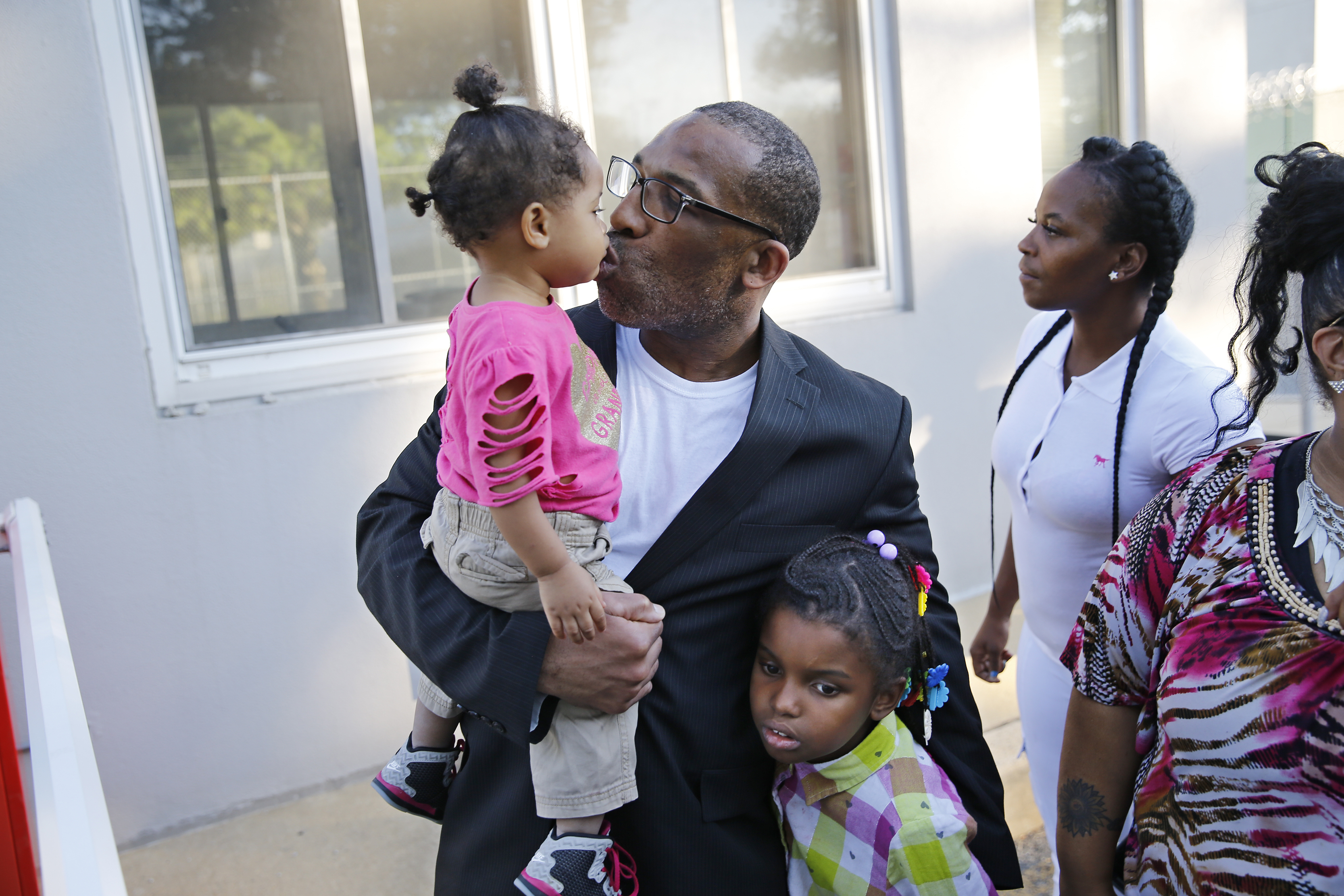 Anthony Wright, steals a kiss from granddaughter Romera Wright, 1, and hugs granddaughter, Daria, Wright, 8, after walking out of Curran Fromhold Correctional Facility a free man on Tuesday August 23, 2016.