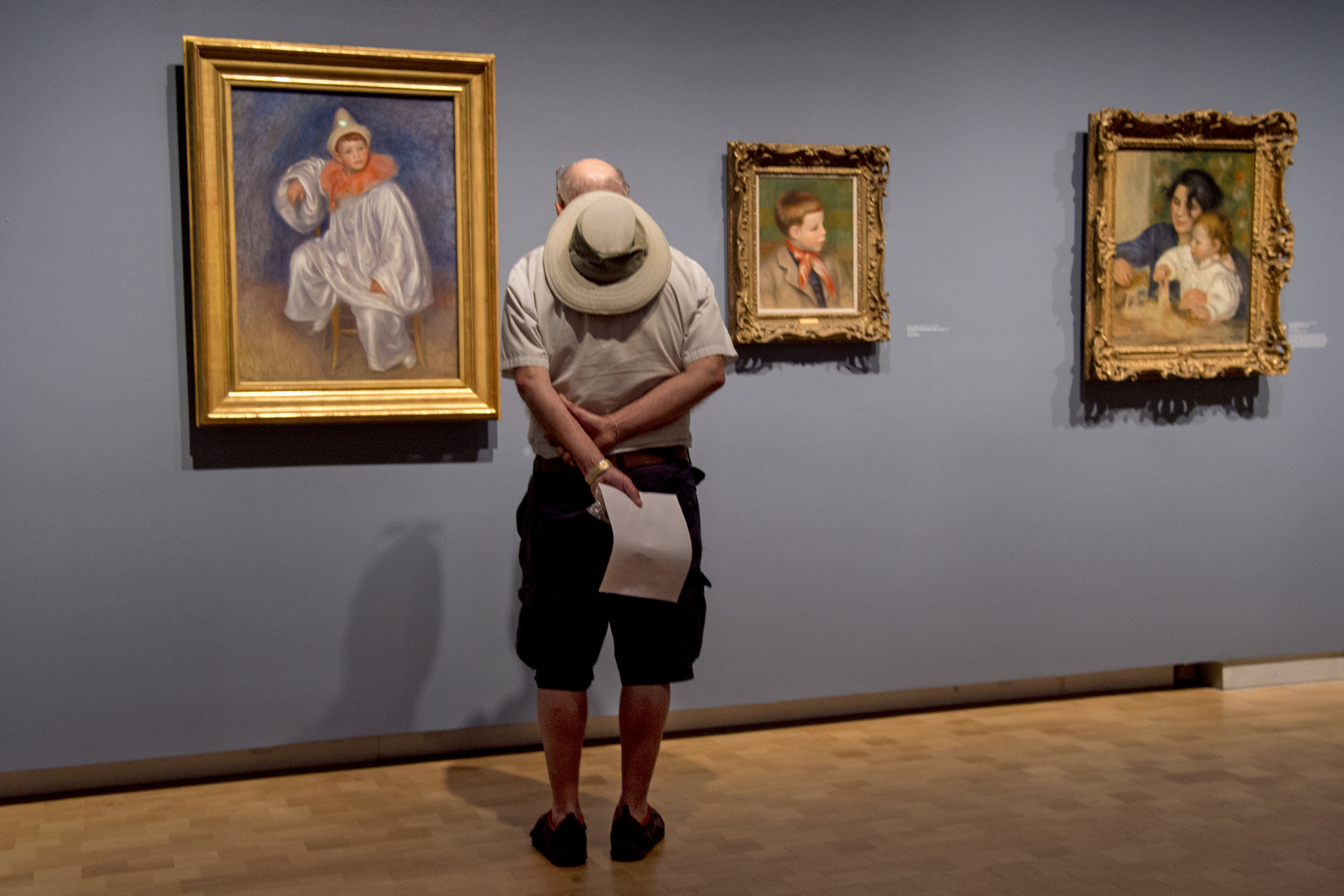 """Rich Kato looks over the paintings in the """"Renoir: Father and Son / Painting and Cinema"""" exhibit at the Barnes Foundation June 3, 2018, during Free First Sunday Family Day and the Barnes´ first ever free block party. The paintings are by artist Pierre-Auguste Renoir, of his son, director Jean Renoir, when he was a child."""