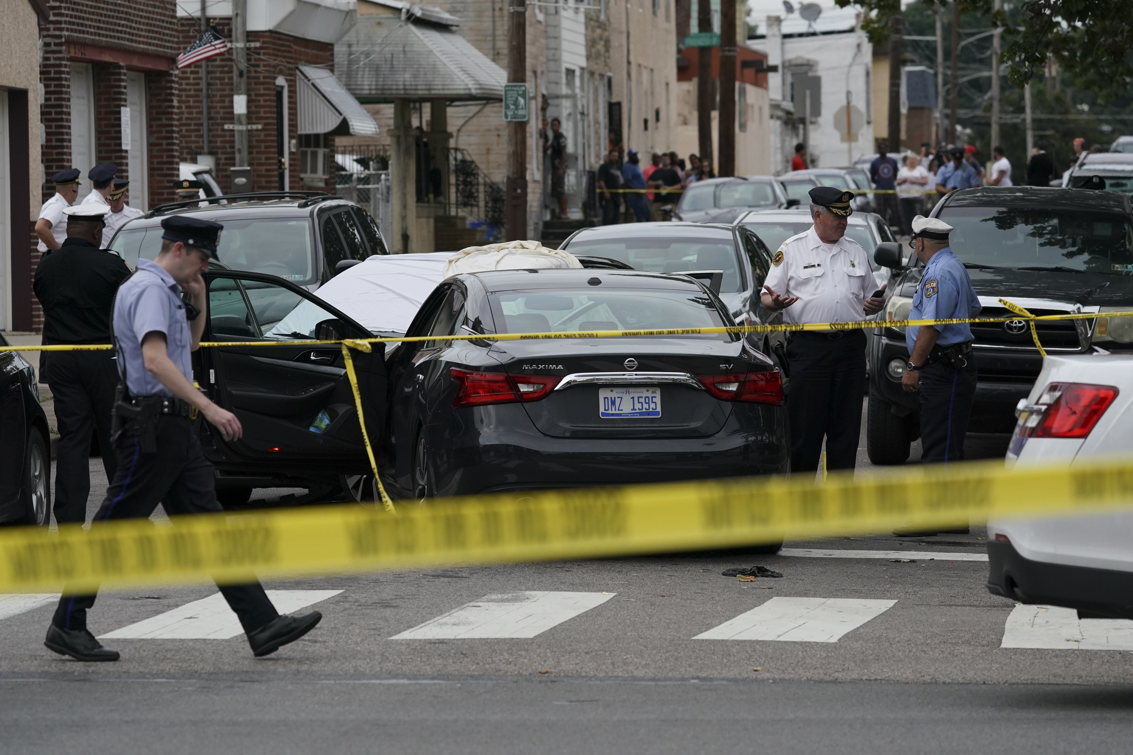 Investigators gather at the crime scene on Hegerman Street near Princeton Avenue in the Tacony section of Philadelpia, Monday Aug. 20, 2018, after police fatal shot a man.