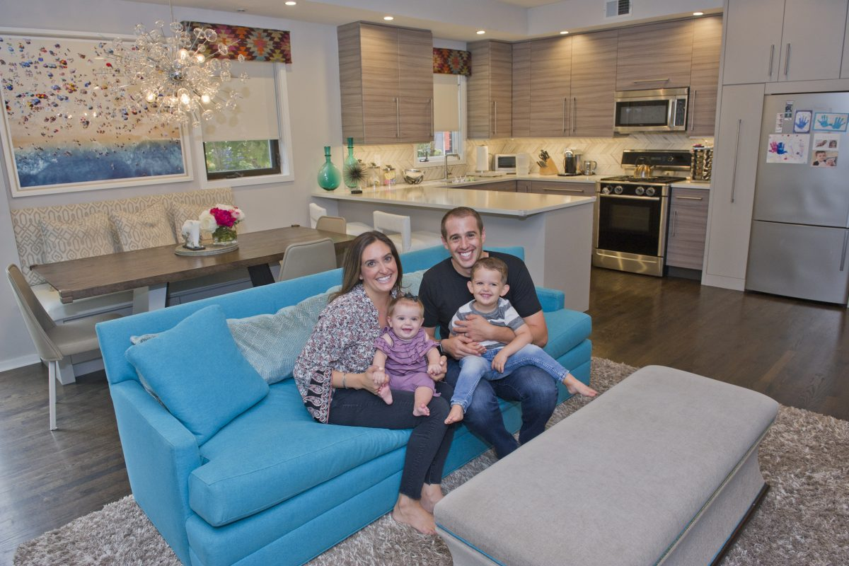 Paige and Ray Jaffe with their daughter Noa, 8 months, and son Max, 2½, in the open living room, kitchen, dining room of their Fitler Square/Rittenhouse area townhouse. When they remodeled, they picked a teal sofa to pop to their neutral decor.