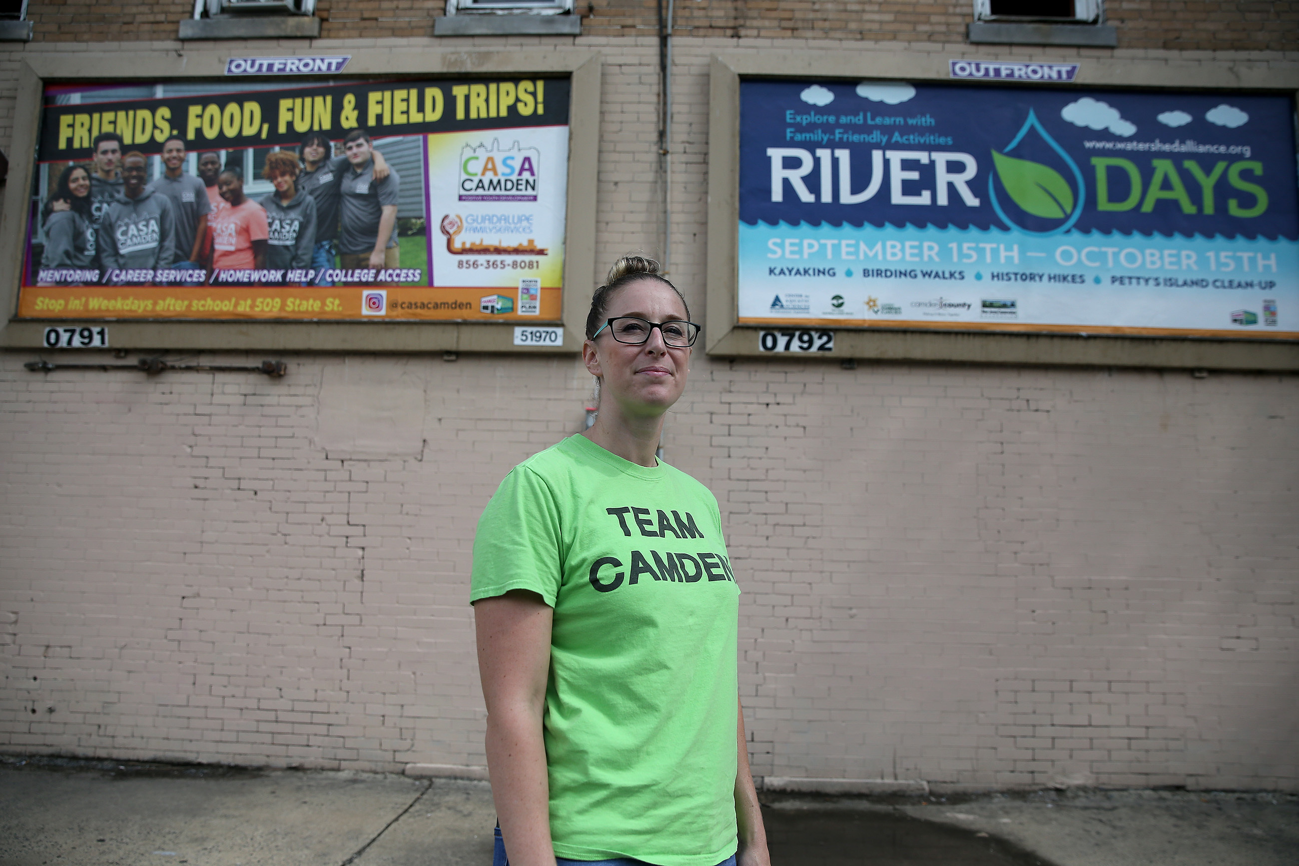 Jessica Franzini, of Camden Lutheran Housing Inc., stands in front of two billboards at 7th and Elm Streets in Camden, DAVID MAIALETTI / Staff Photographer