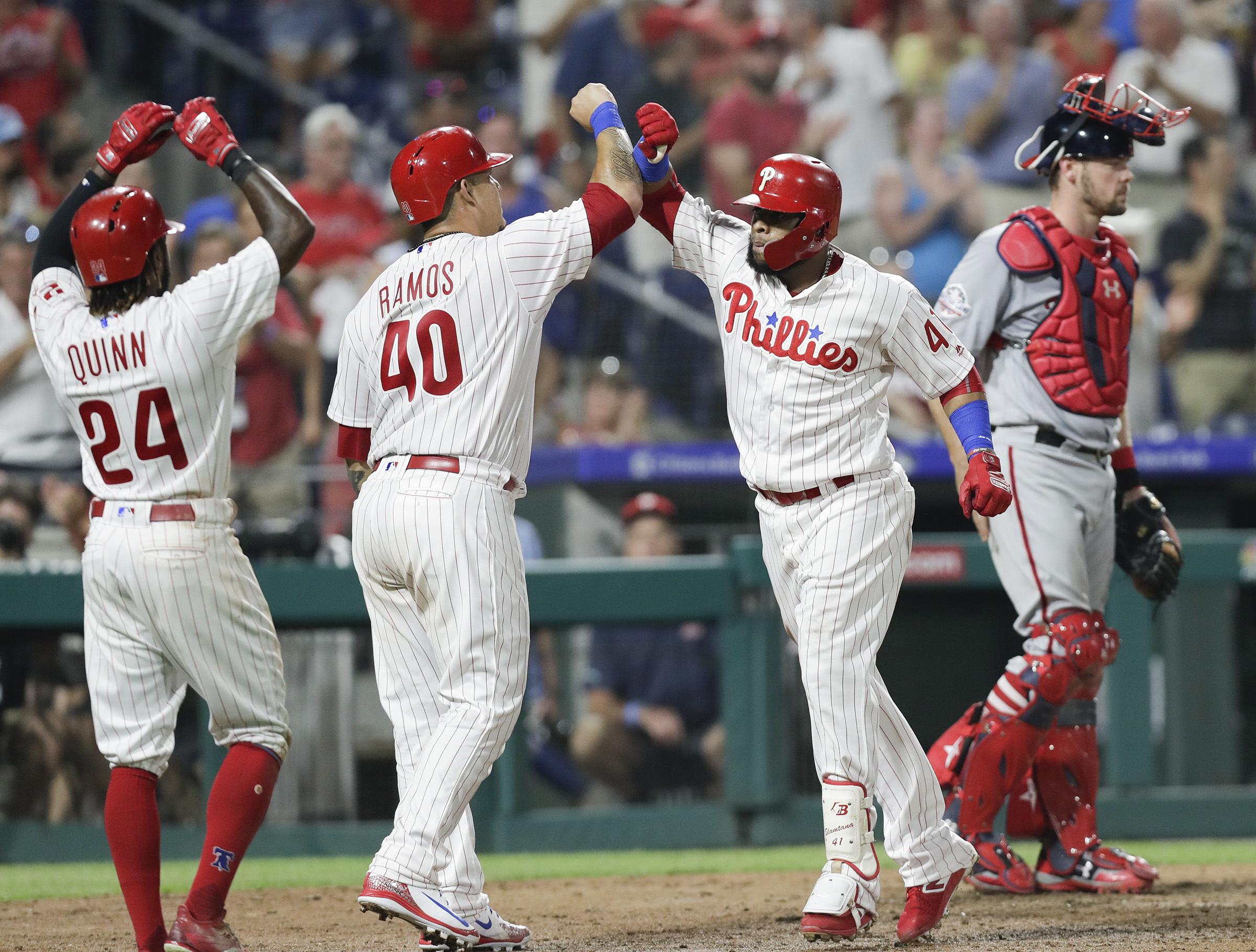 Carlos Santana celebrates his fifth-inning grand slam with teammates Wilson Ramos and Roman Quinn Wednesday night.