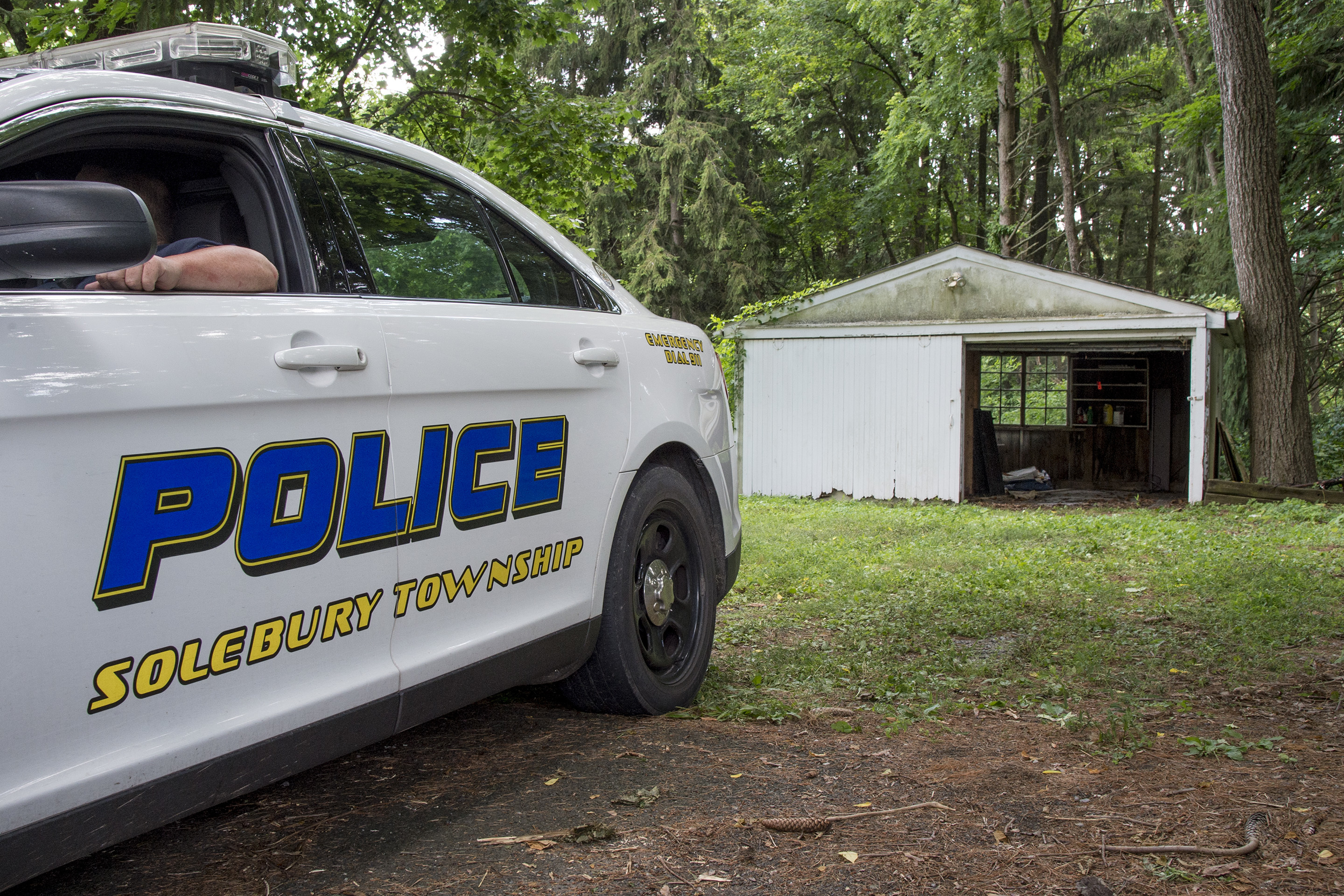 A Solebury Township policeman guards a garage on Aquetong Road where investigators found the car of one of the four missing men. (CLEM MURRAY / Staff Photographer)