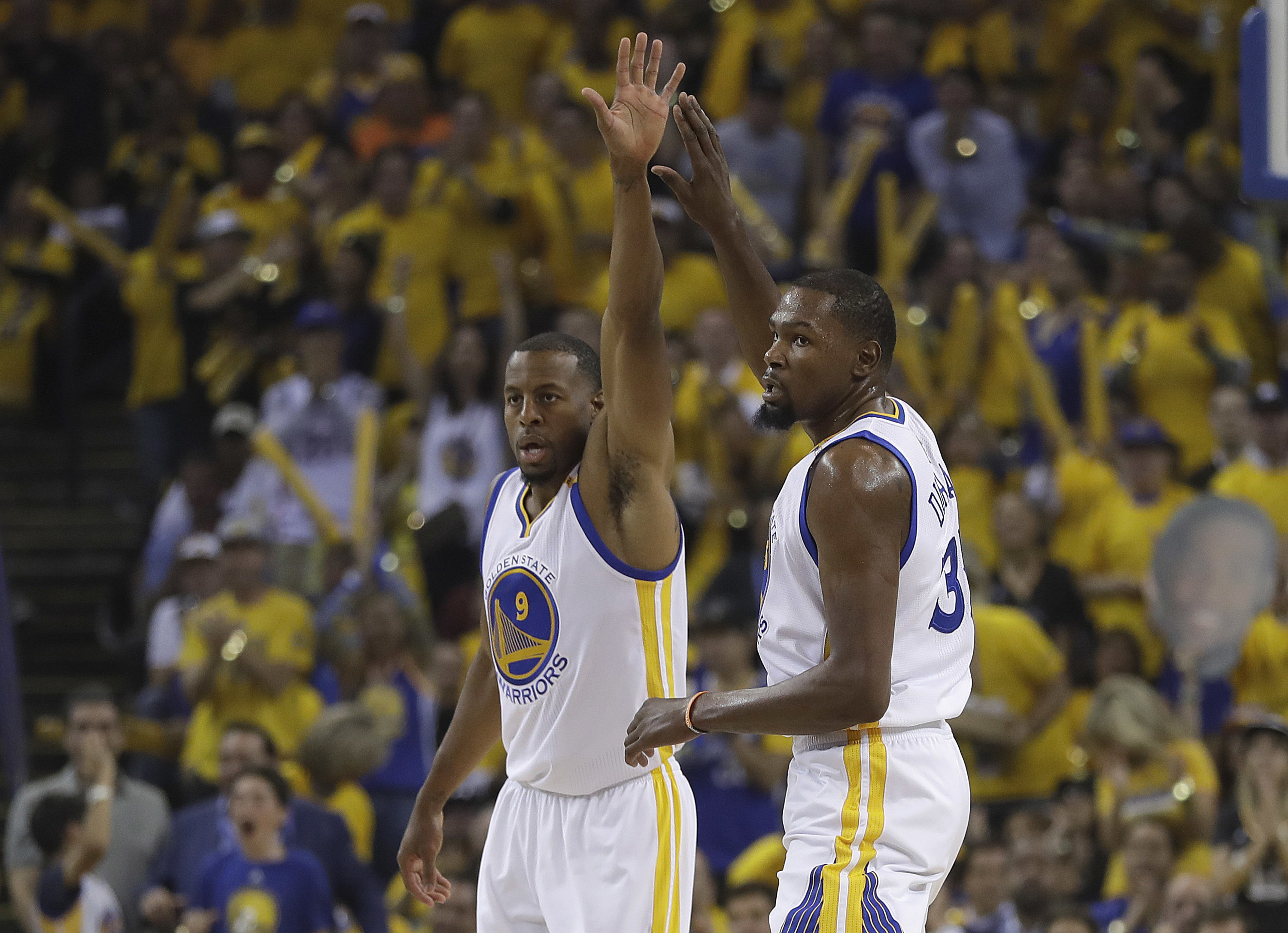Golden State Warriors forward Andre Iguodala (9) and forward Kevin Durant (35) react after scoring against the Cleveland Cavaliers during the first half of Game 1 of basketball´s NBA Finals in Oakland, Calif., Thursday, June 1, 2017. (AP Photo/Marcio Jose Sanchez)