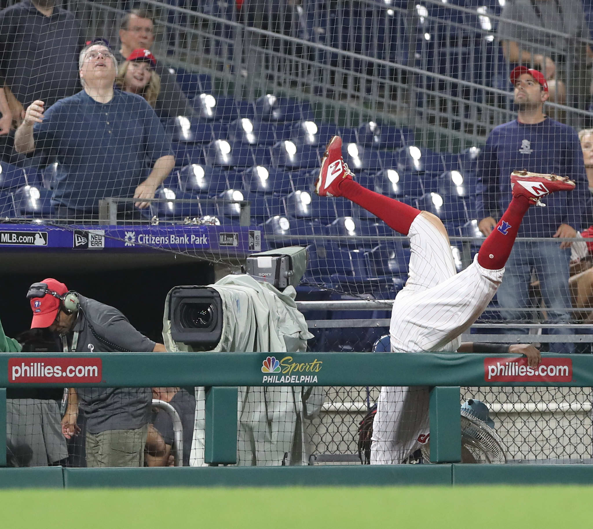 Maikel Franco, right, of the Phillies flips over a railing as he goes after a foul ball hit by Adam Eaton of the Nationals in the 8th inning at Citizens Bank Park on Sept. 11, 2018.