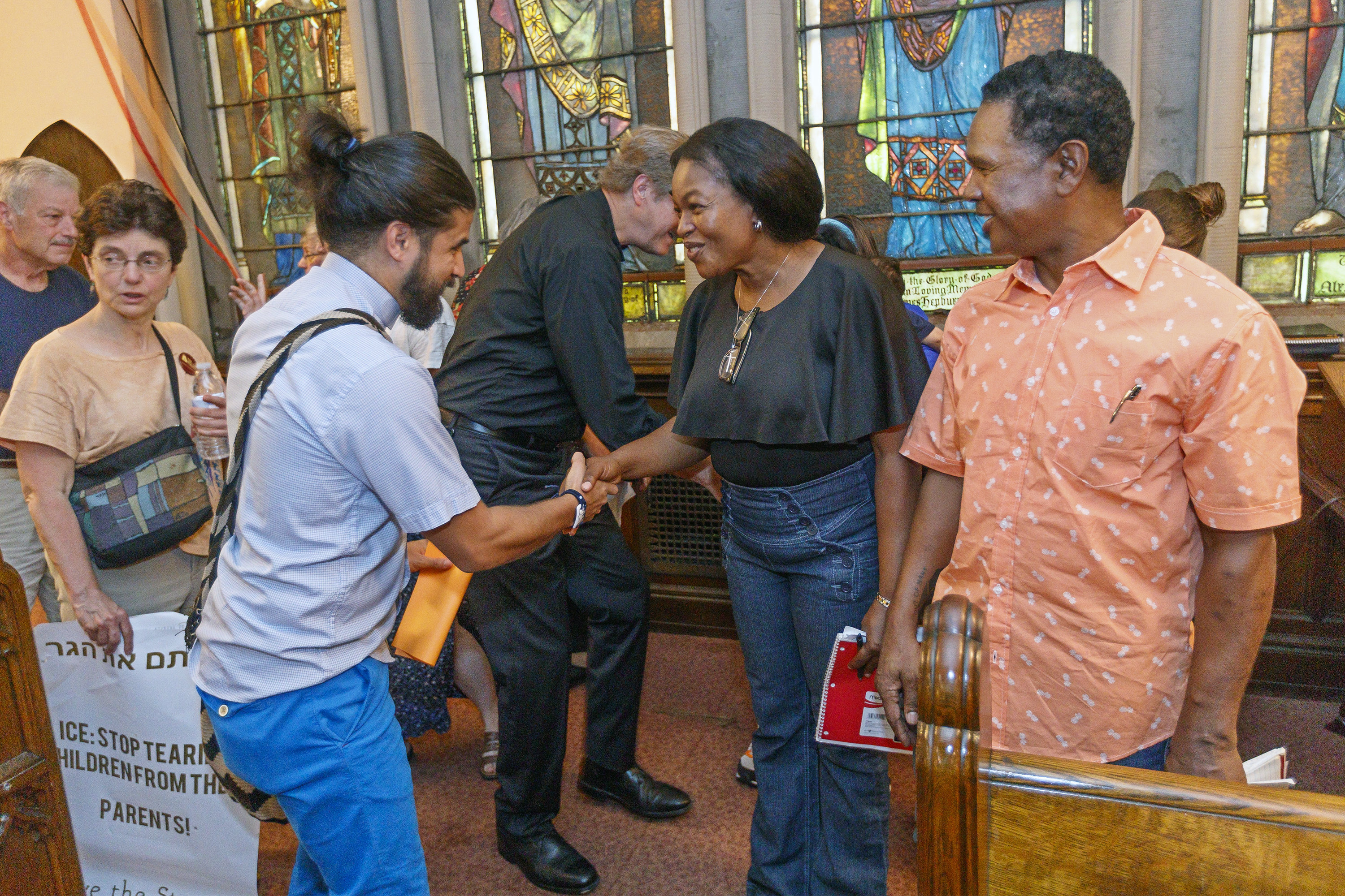 Oneita Thompson, center, and her husband Clive Thompson, right, originally from Jamaica, are greeted by well-wishers in the First United Methodist Church of Germantown, on September 5 as part of a welcoming ceremony at the church for the two families who took sanctuary there.
