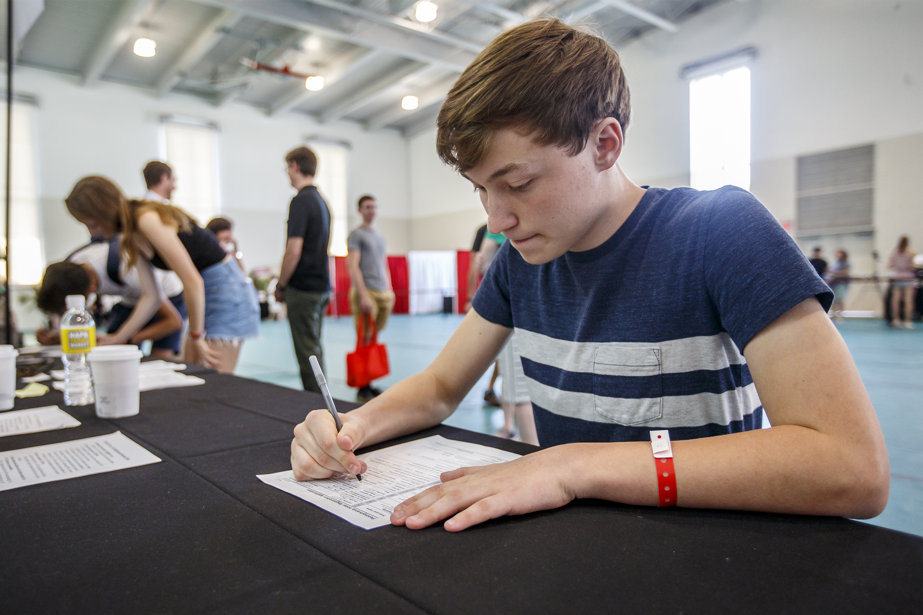 """Incoming Haverford College freshman John Ratliff, 18, of New Jersey fills out a voter registration form. He says having an on-campus polling place """"will draw more students in."""""""