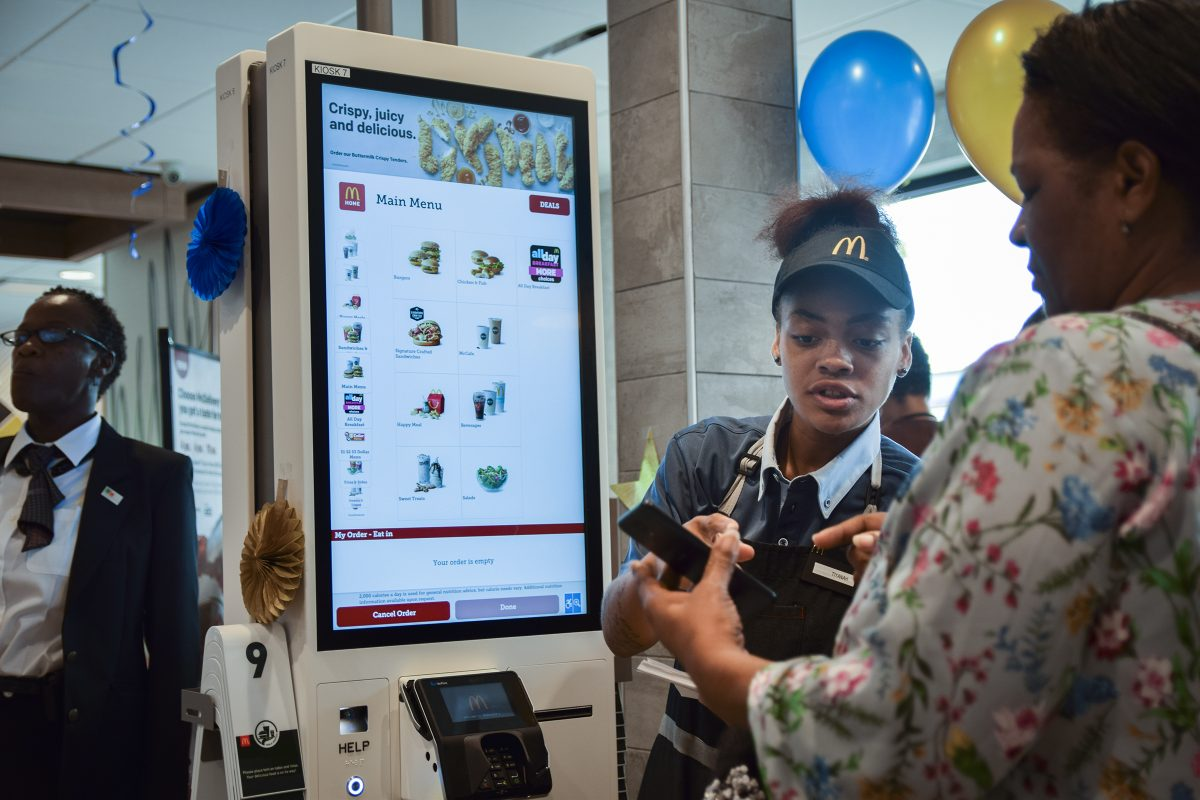 McDonalds employee Tiyanah Boyd assists customer Judy Dixon (right) with the new technology in the McDonald's at 7500 City Ave.