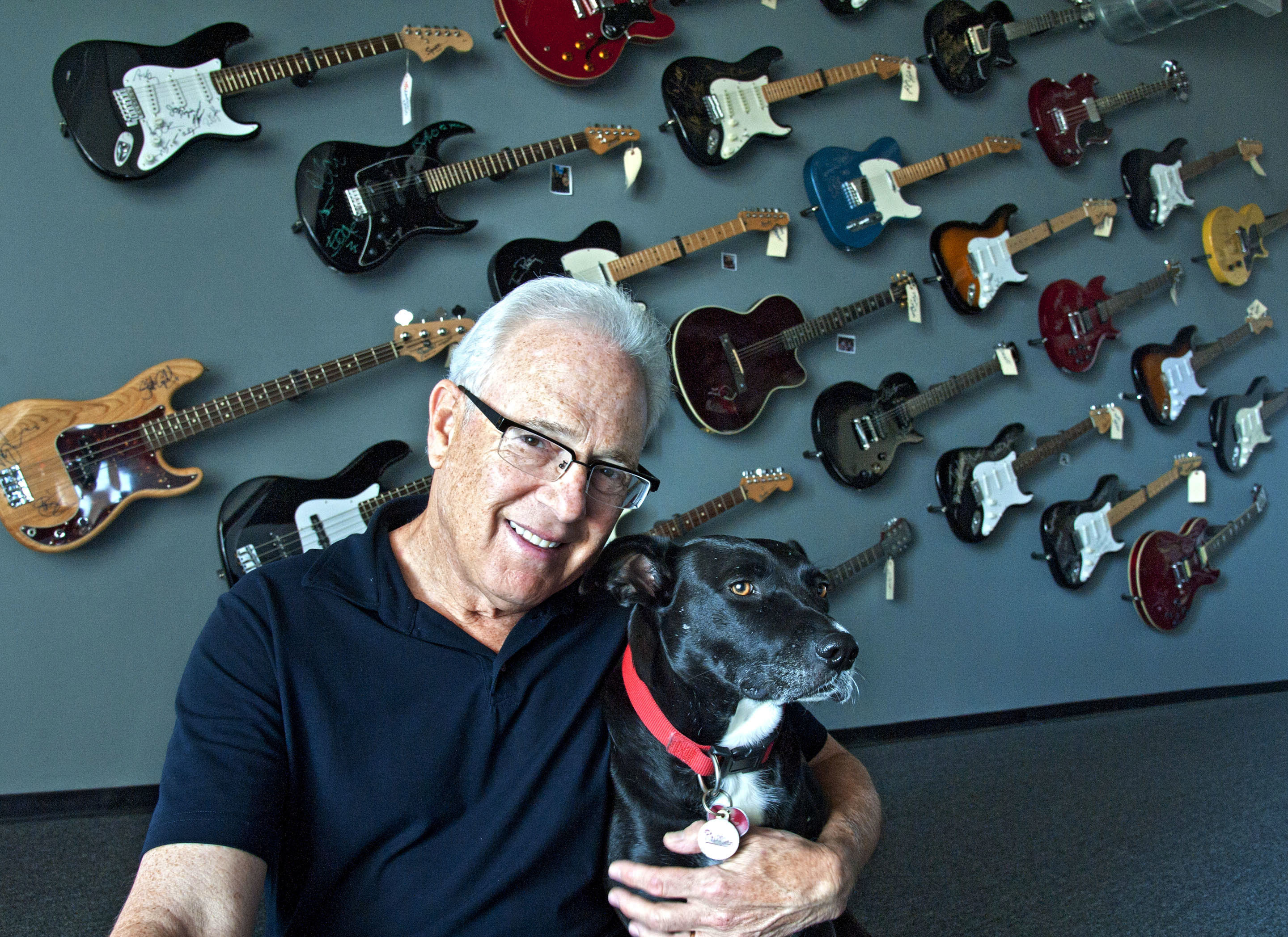Portrait of Larry Magid, cofounder of Electric Factory Concerts, with his dog Midnight in the lobby of his company´s offices located at the Piazza at Schmidt´s.