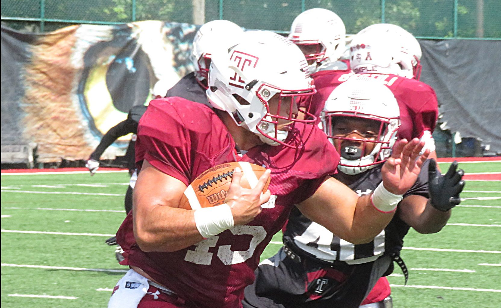 Temple LB Todd Jones (40) pursues fellow former walk-on and RB Rob Ritrovato during a training camp practice.