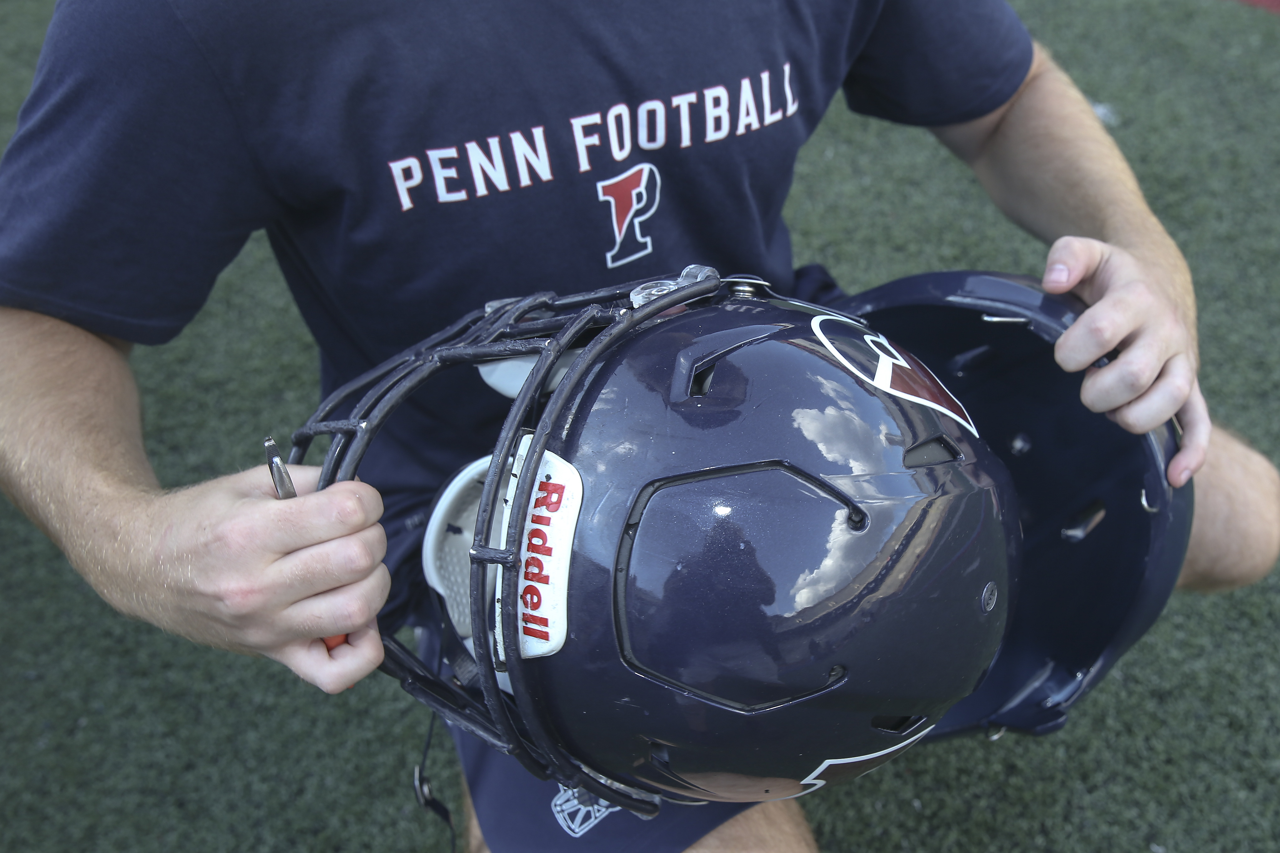 Penn´s assistant equipment manger Tyler Piccotti shows how the helmet cover comes apart after practice at Franklin Field, Thursday, August 30, 2018. STEVEN M. FALK / Staff Photographer