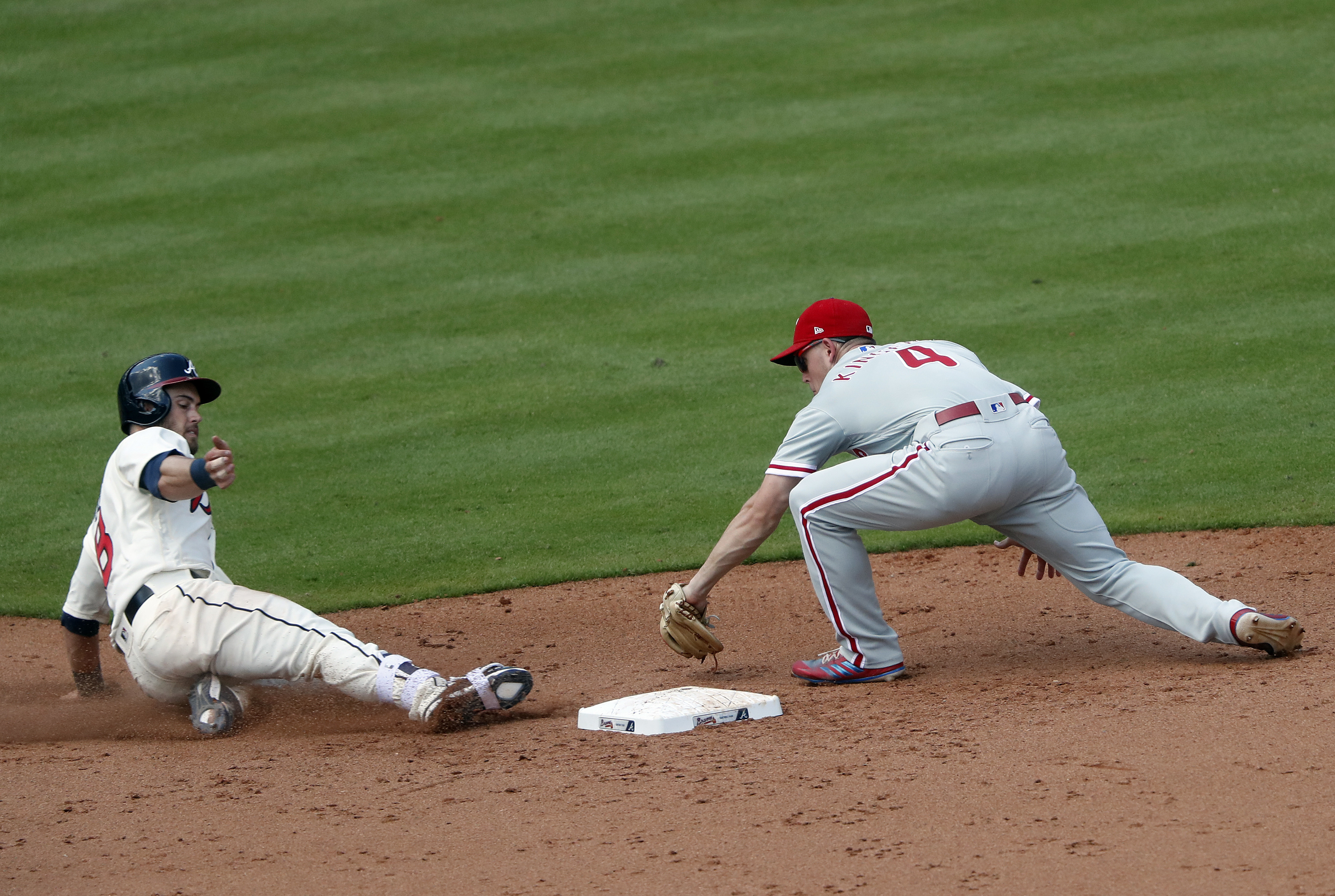 The Braves� Preston Tucker slides ahead of the tag from Phillies second baseman Scott Kingery after a fielding error by third baseman Maikel Franco in the sixth inning of Sunday�s loss.