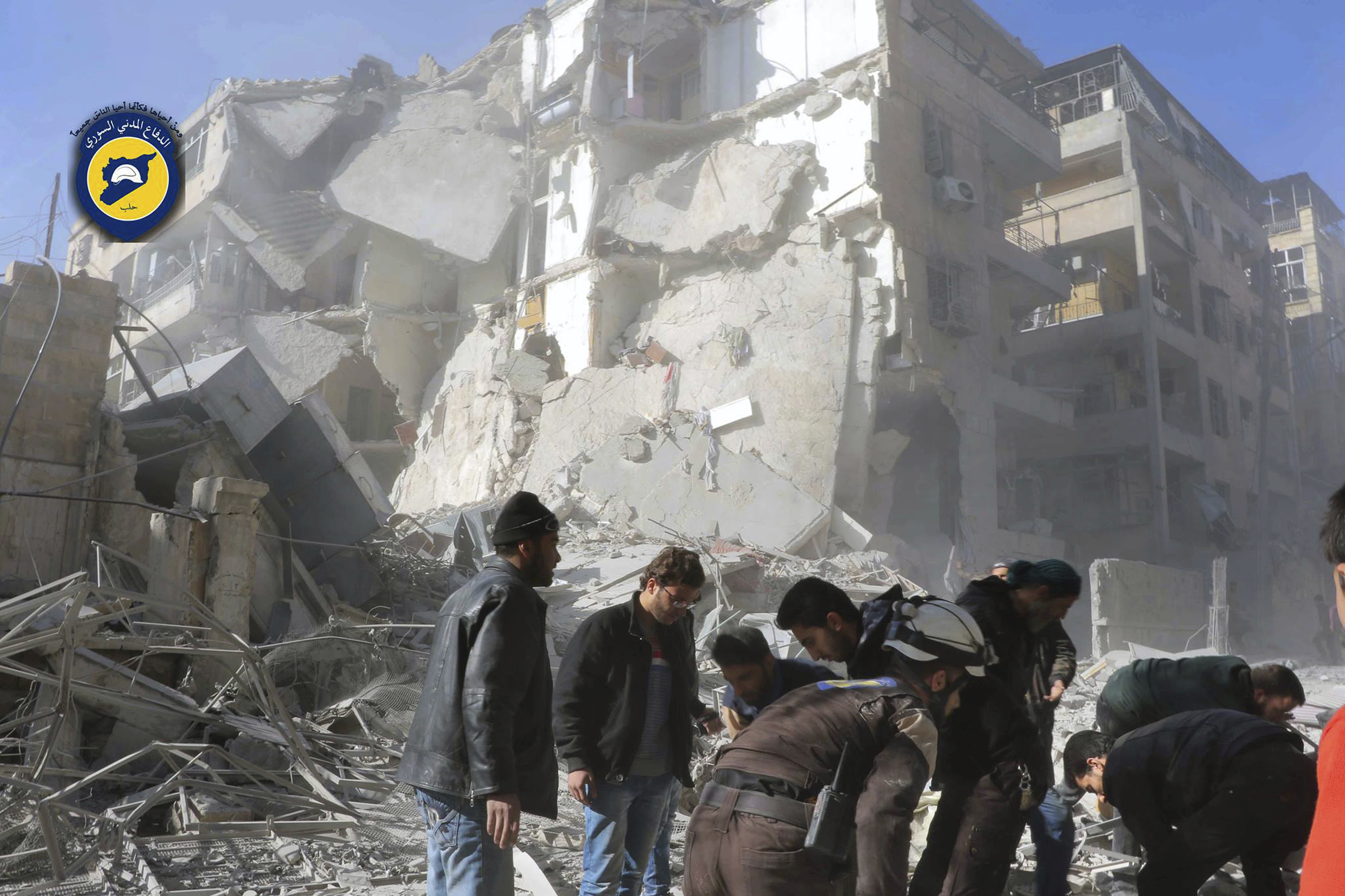 This photo provided by the Syrian Civil Defense White Helmets, which has been authenticated based on its contents and other AP reporting, shows Civil Defense workers and Syrian citizens inspect damage buildings after airstrikes hit the Seif al-Dawleh neighborhood in Aleppo, Syria, Saturday, Nov. 19, 2016.
