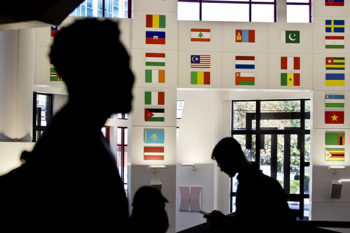 Students walk through Temple's student center, where flags are displayed to represent the home countries of members of Temple's student body.