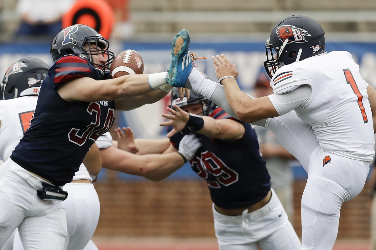 Penn linebacker Patrick McGettigan blocks a first-quarter punt by Bucknell's Alex Pechin. The Quakers took advantage of early defensive momentum to seal the season-opening win.