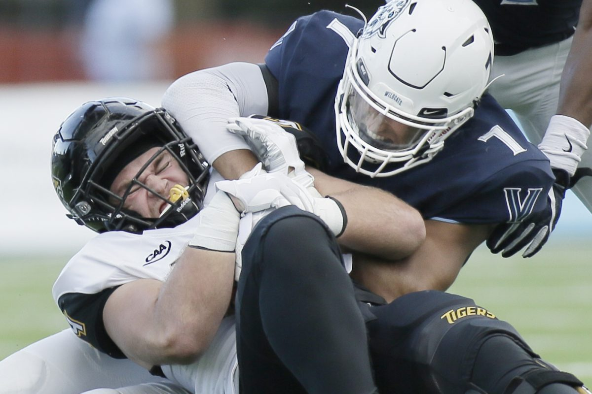 Towson's Zach Heron is stopped by Villanova's Julian Williams in the 3rd quarter last Saturday.
