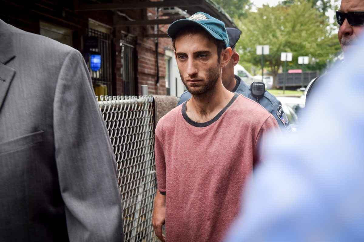 Robert Coult III walks to a police vehicle outside the Yeadon Police Department on Monday. Coult is accused of murdering his father and dumping his body in Lower Merion Township.