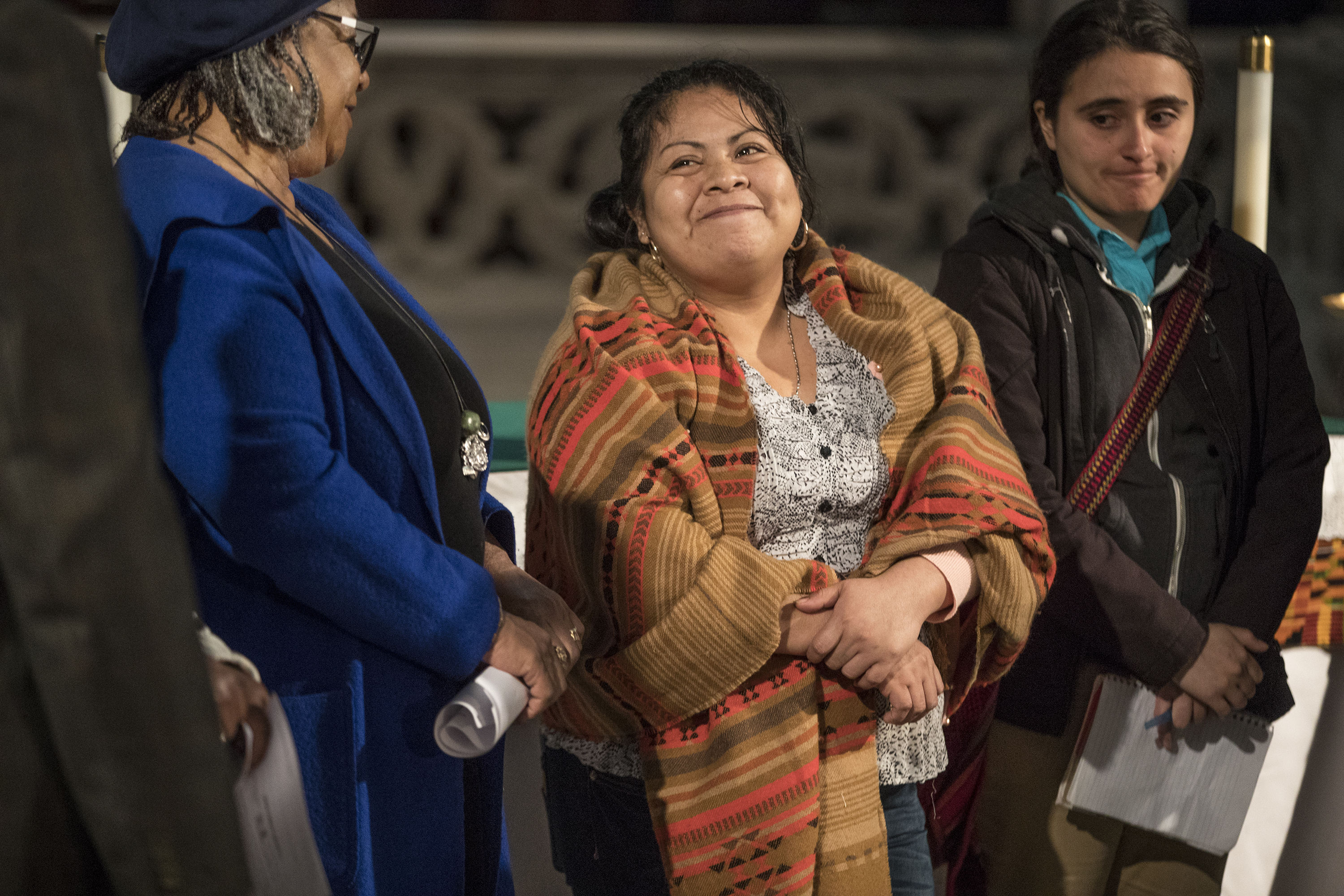 Carmela Apolonio Hernandez, center, smiles as speakers support her cause for immigration relief during a press conference at the Church of the Advocate in April.