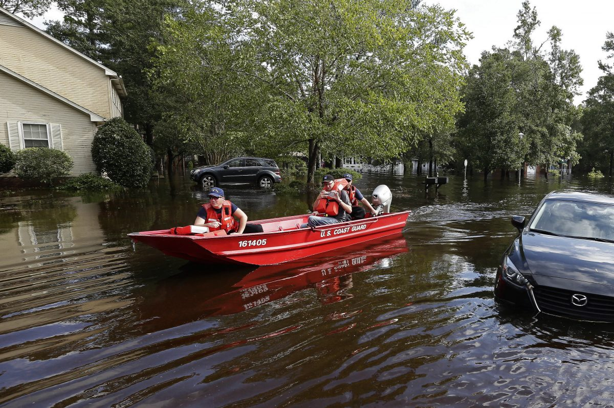 Members of the U.S. Coast Guard Shallow Water Rescue Team check on a flooded neighborhood in Lumberton, N.C., Monday, Sept. 17, 2018, in the aftermath of Hurricane Florence. (AP Photo/Gerry Broome)