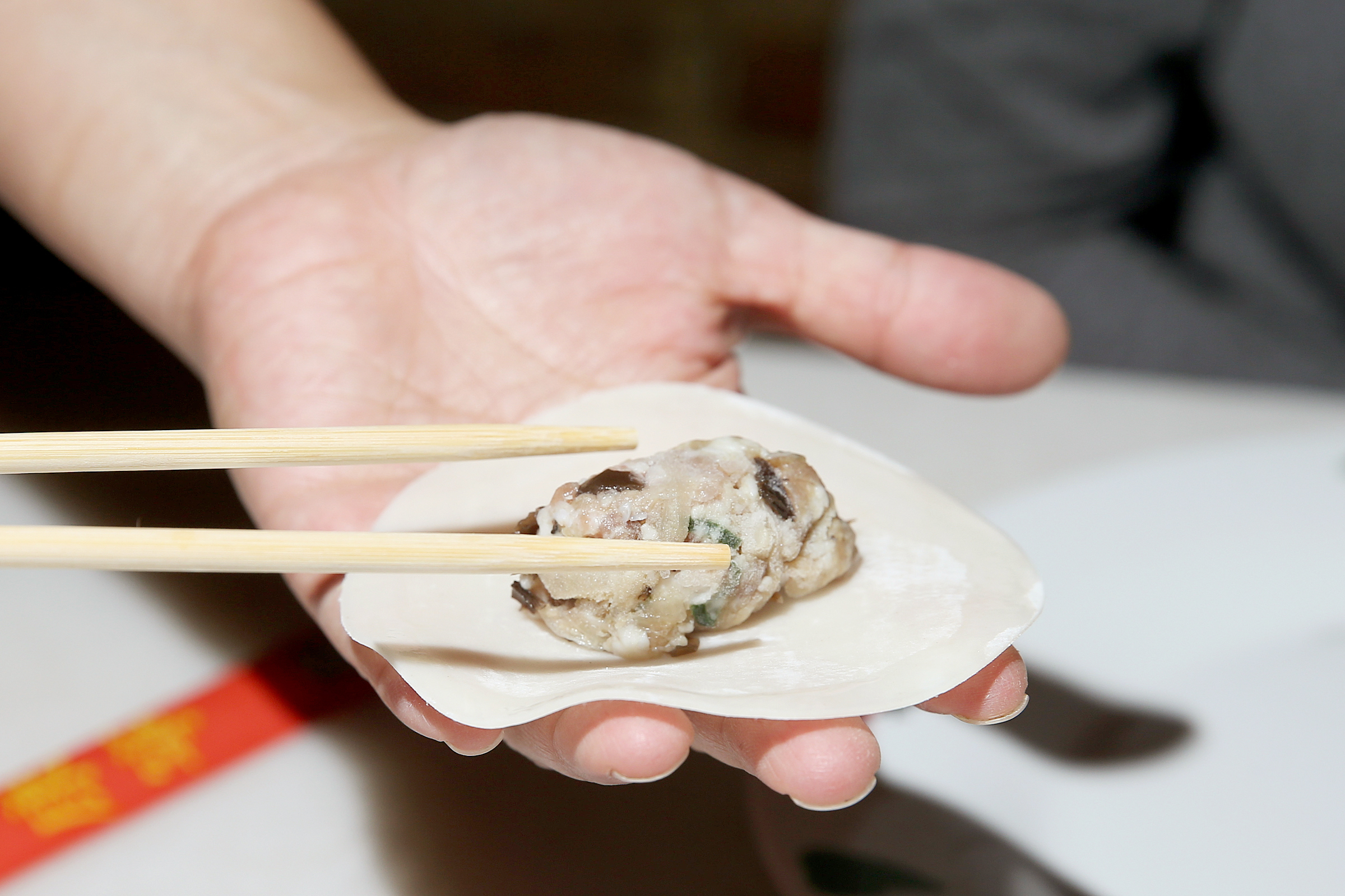 """Chef-owner Ange Branca demonstrates how to wrap your own dumplings at Saté Kampar in South Philadelphia on Wednesday, Sept. 19, 2018. The restaurant is offering a reservation-only """"Crazy Rich Asians"""" themed dinner."""