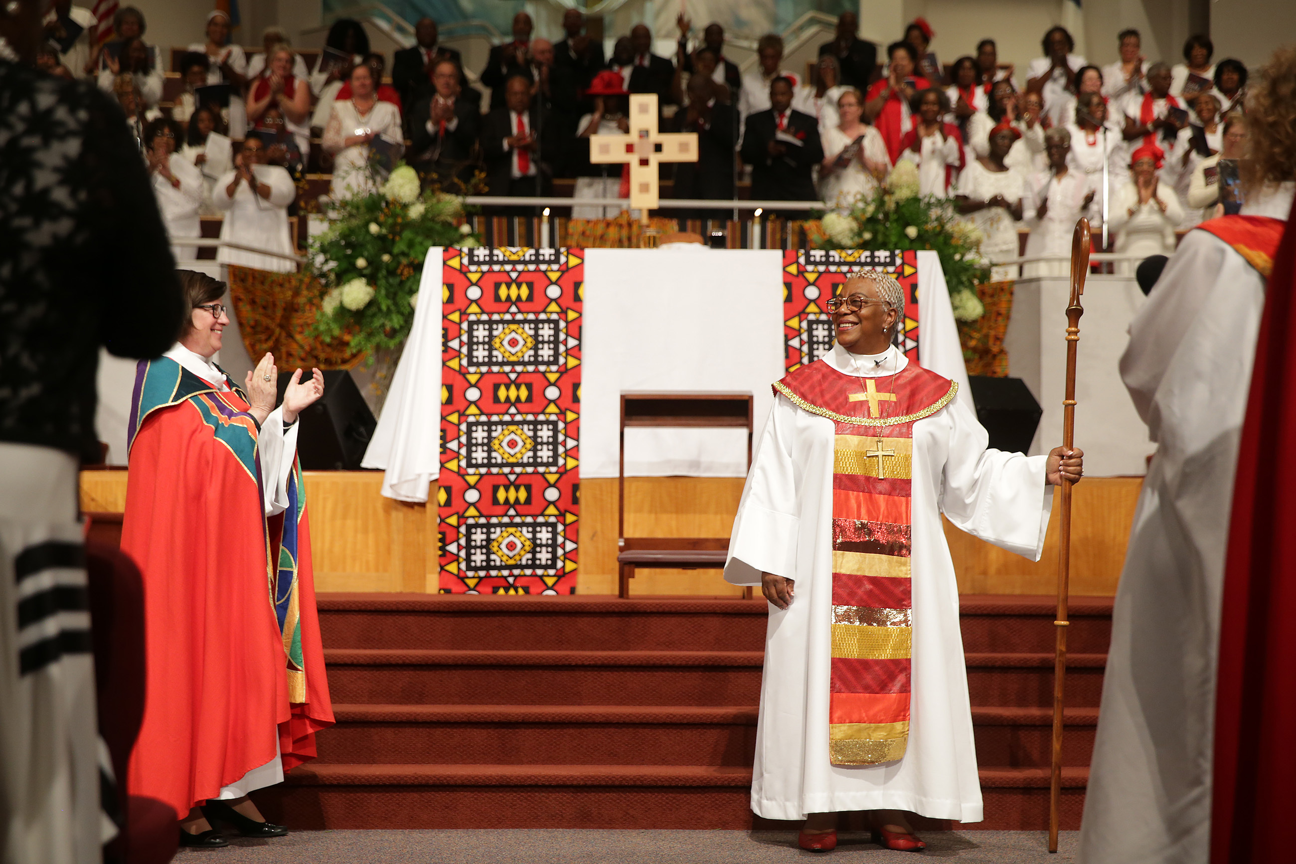 The Rev. Elizabeth Eaton (left) applauds as Bishop Davenport is installed.