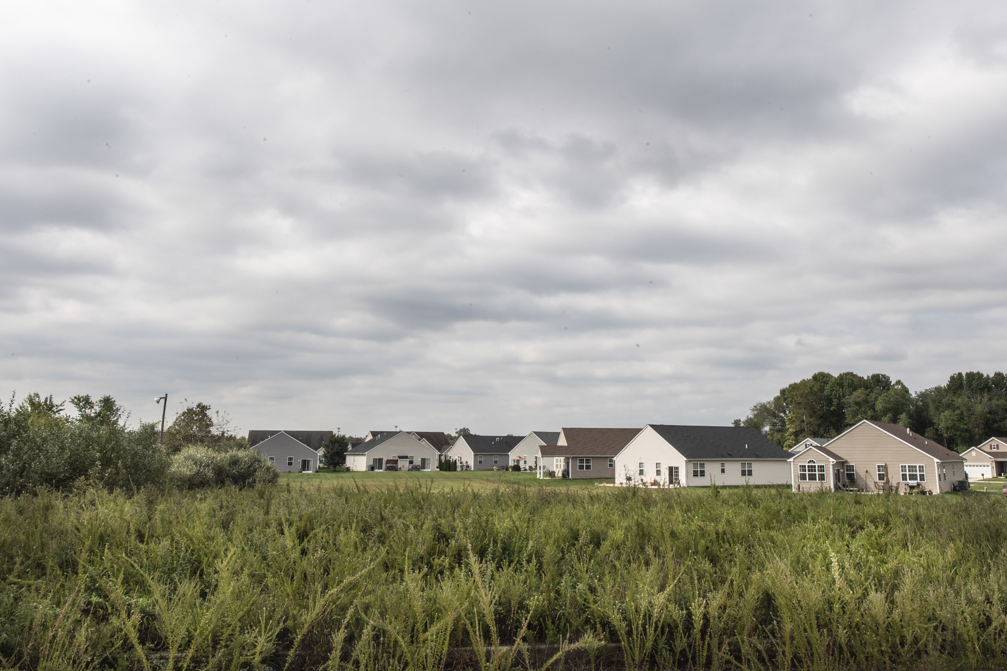 A view of open land with housing behind it is shown at the Cenco Boulevard Industrial Park, in Clayton, New Jersey.
