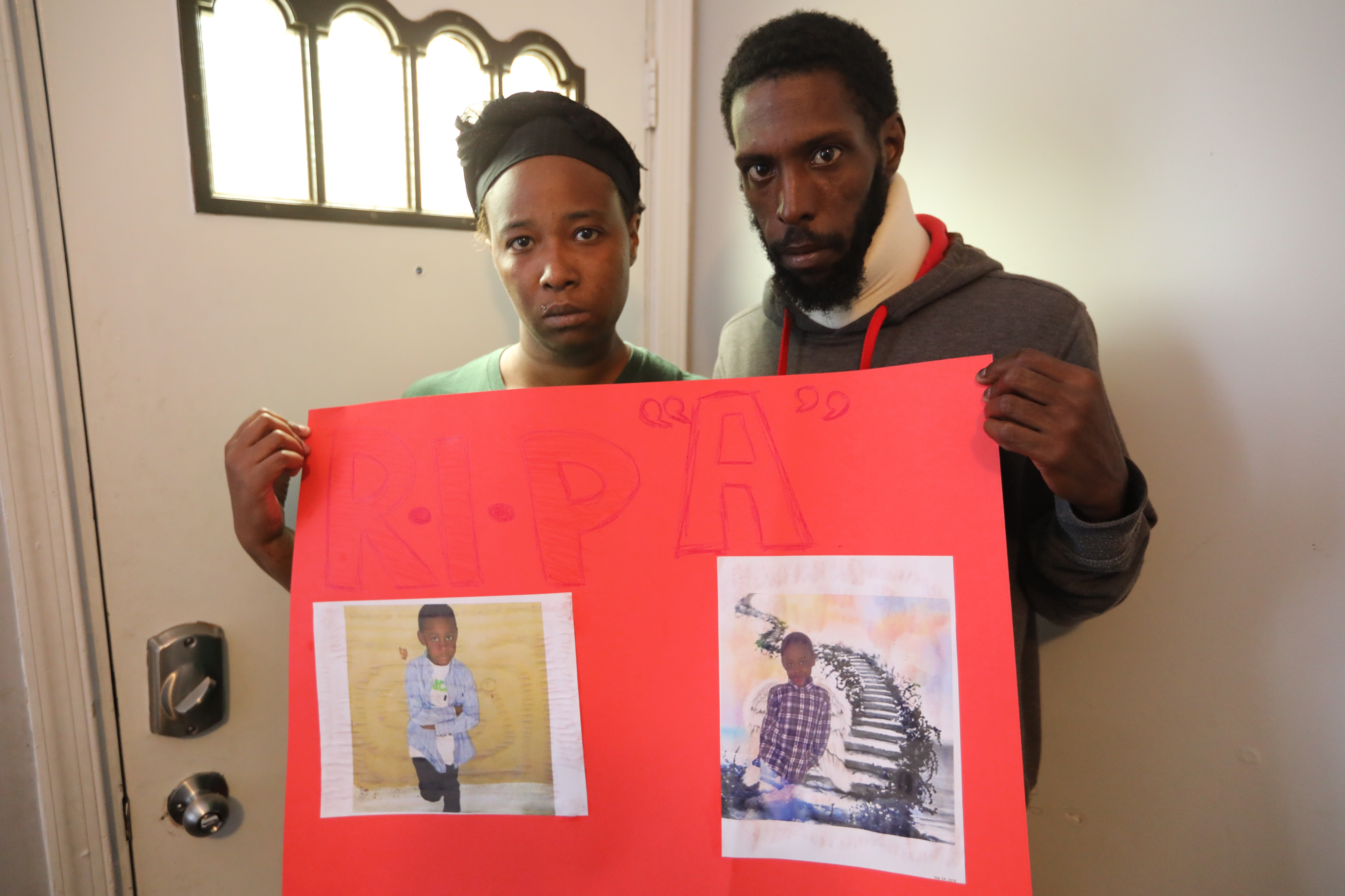 Mother and father Kimberly Dantzler, 29.And Troy Devlin, 36, hold a poster of their son Aden Devlin, 7, who lost his life yesterday after falling from a Septa Subway train while moving from one car to another while the the train was in motion, Monday September 24, 2018.