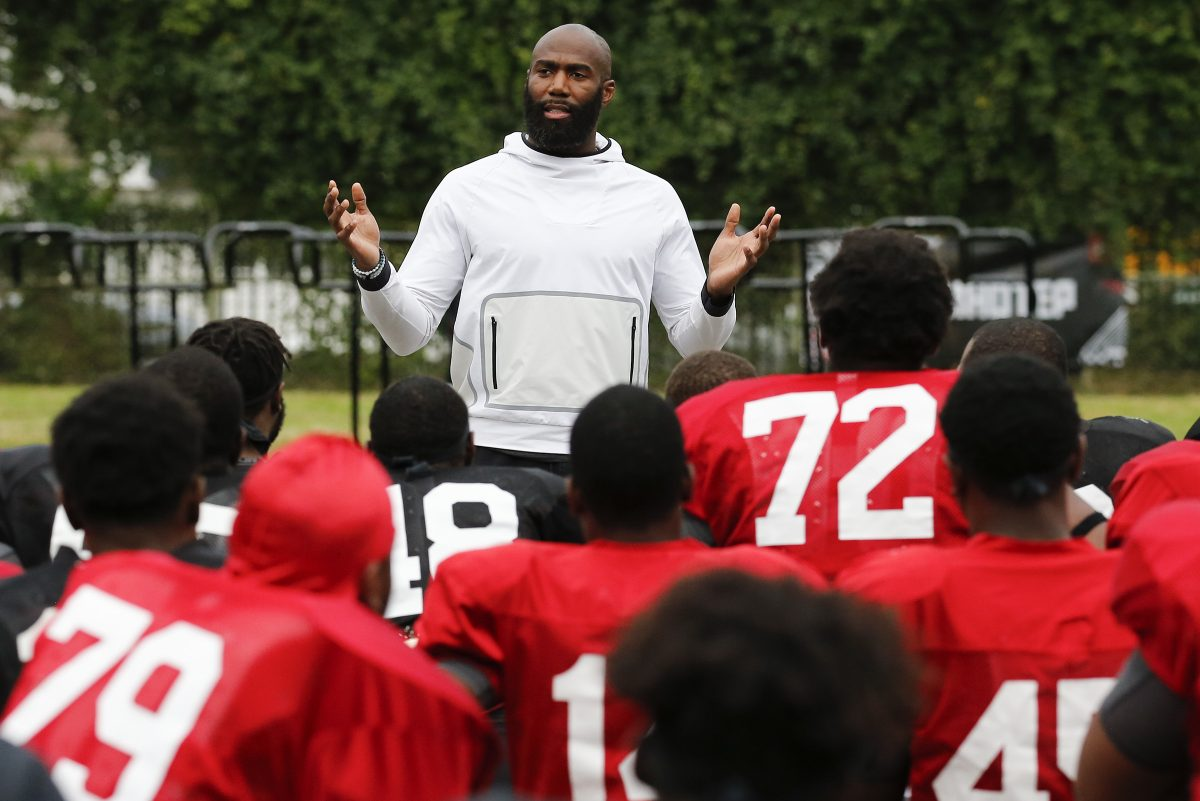 Eagles safety Malcolm Jenkins addresses Imhotep Charter's football players during Monday's practice.