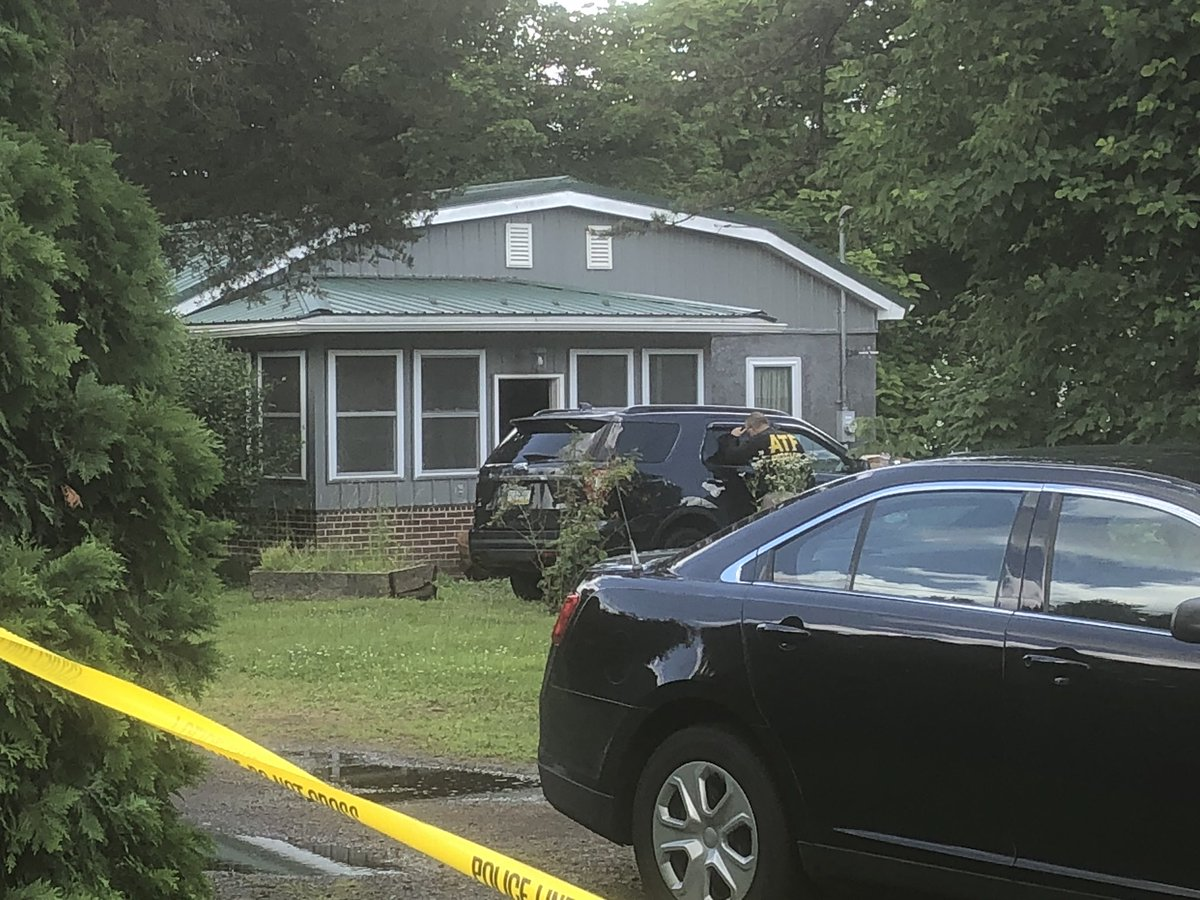 An investigator from the Bureau of Alcohol, Tobacco, Firearms and Explosives investigates the home of David Surman Jr. on June 28. Officials seized four explosive devices from the home, one of which was 18 inches long.