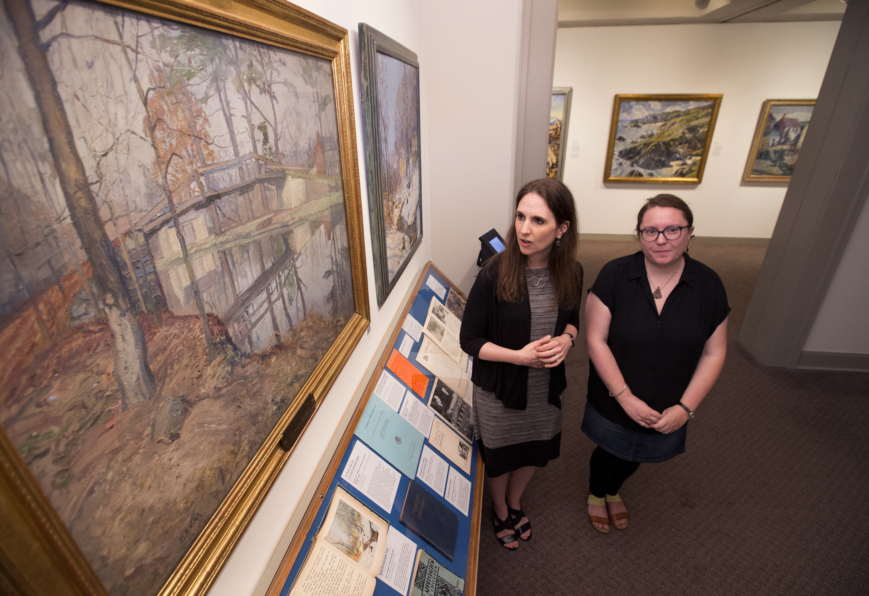 """The Philadelphia School District´s valuable art collection that were abruptly removed from the school walls where they had hung for decades are now part of a new exhibit at the Michener Museum in Doylestown along with on July 13, 2017. Curator Adrienne Neszmelyi-Romano, left, and Assistant Curator Louise Feder, look over """"Canal Near Point Pleasant"""" by Walter Baum, left. It is part of the collection owned by the School District of Philadelphia. CHARLES FOX / Staff Photographer"""