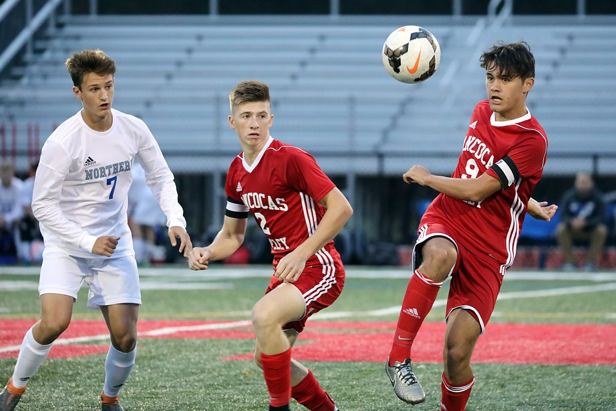 Rancocas Valley's J.C. Johnson right) kicks the ball while teammate Tyler Martin (center) looks on in  a recent game.