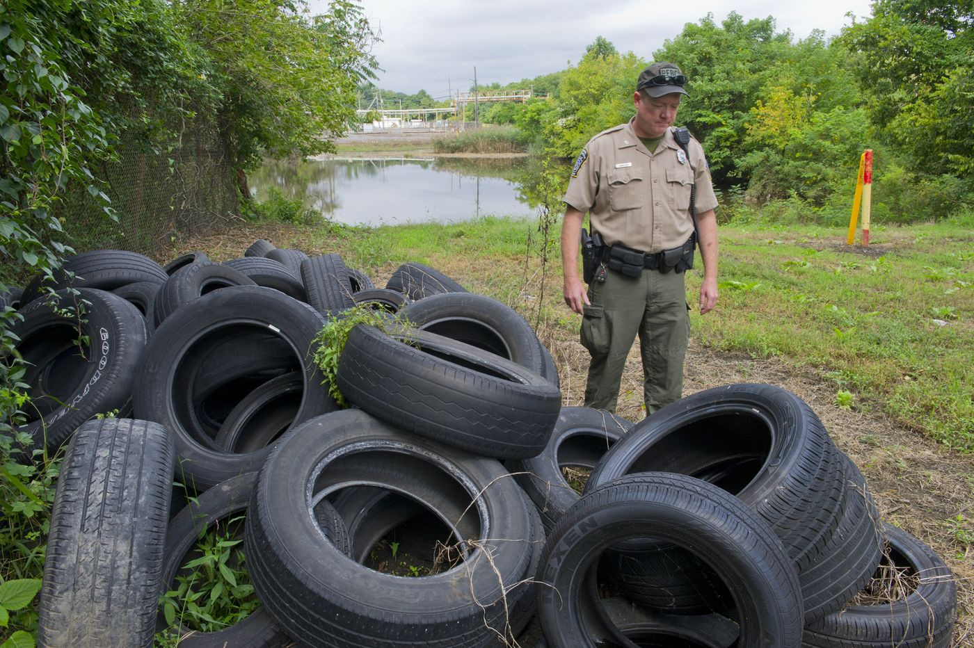PA. Fish and Boat Commission Officer Nathan Hancock inspects an illegal dump of tires in a tributary of the Schuylkill River in South Philadelphia on September 20, 2018.