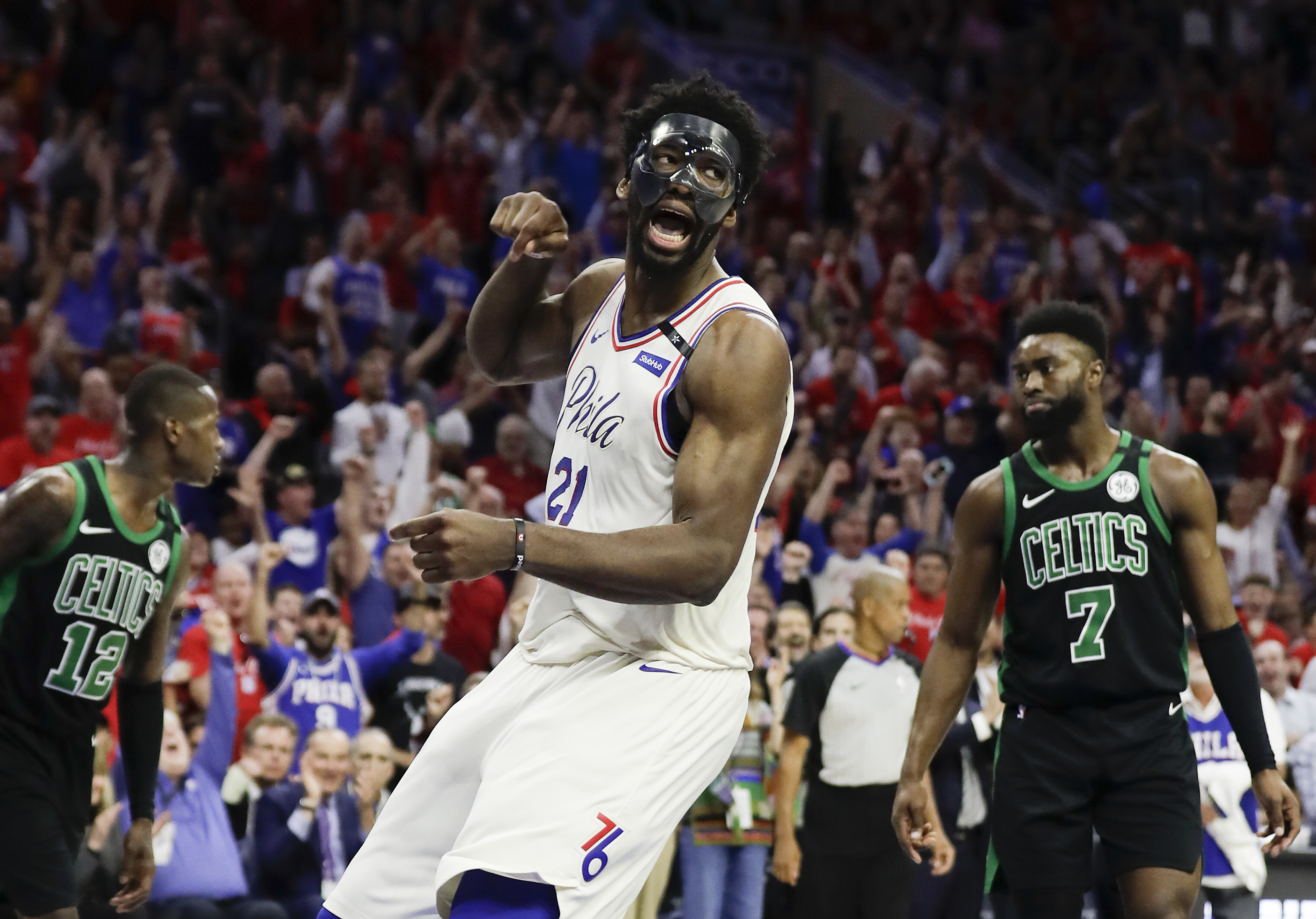 Joel Embiid celebrates after dunking past the Celtics Terry Rozier (left) and Jaylen Brown during the Eastern Conference semifinals.