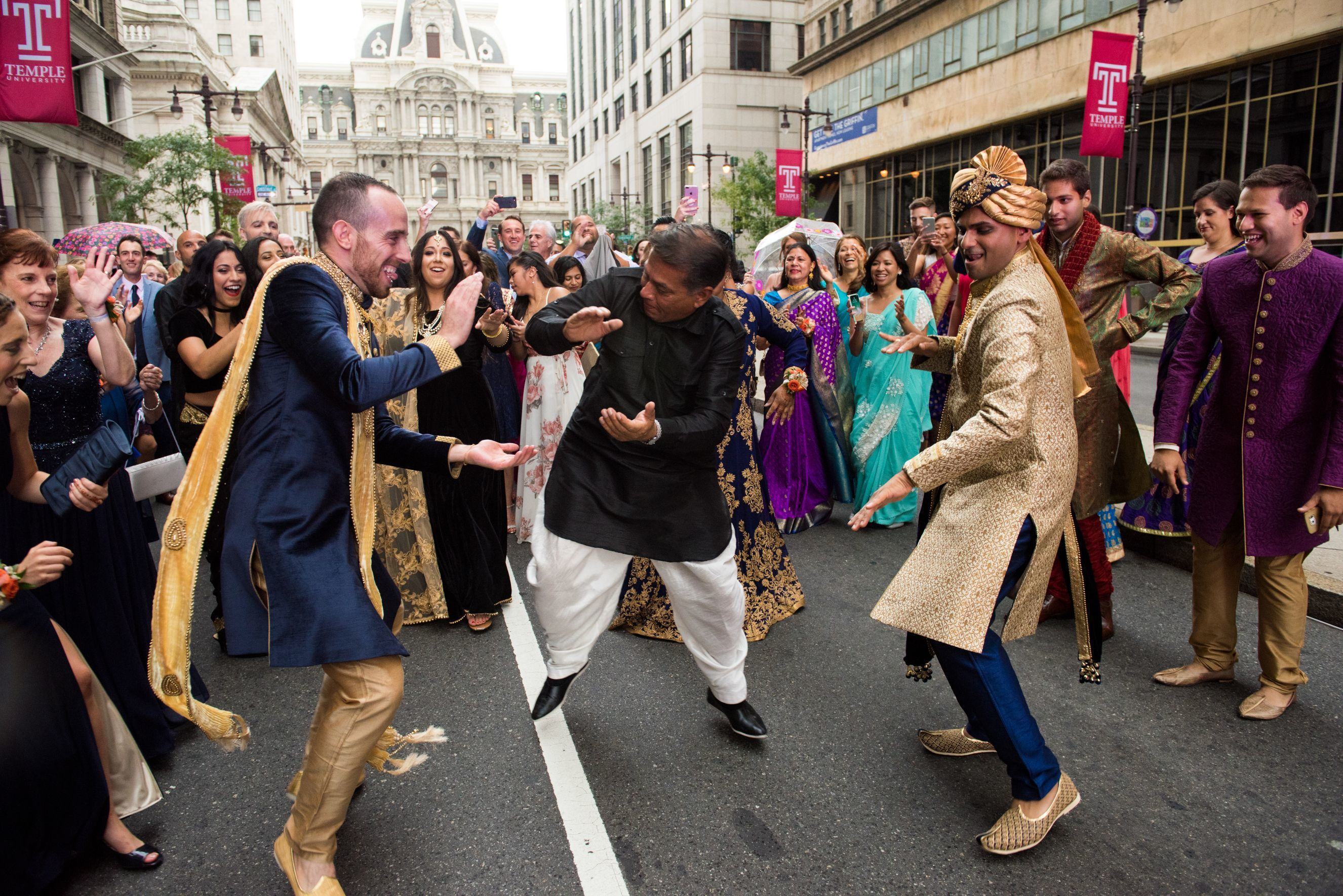 Kyle and Avinash with family and friends, dancing down Broad Street during the baraat ceremony.