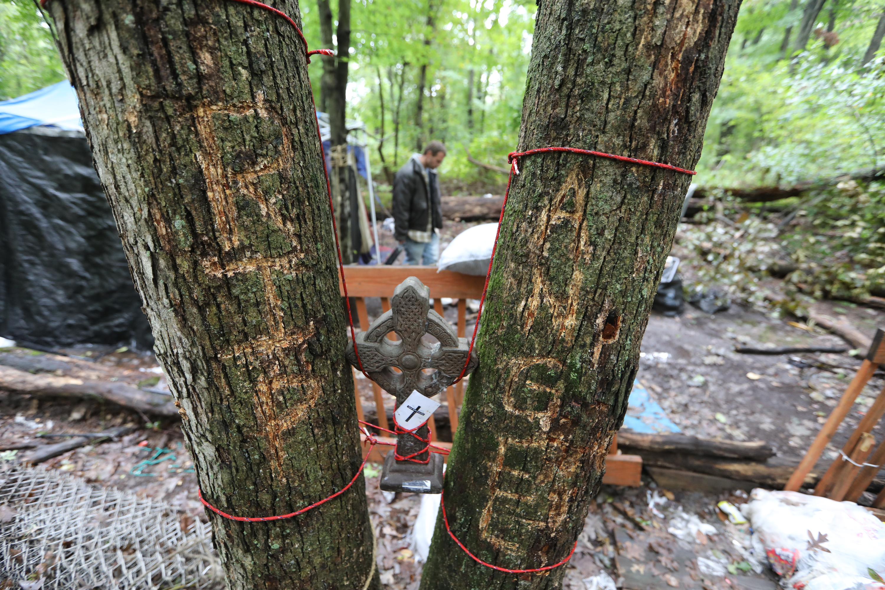 "Brian Winder rummages around the camp where ""RIP Angie"" is carved in a tree, in honor of his mother, who went by that nickname. Beverly Winder, his mother, had been staying at the camp since August, after being evicted from a friend�s house in Northeast Philadelphia."