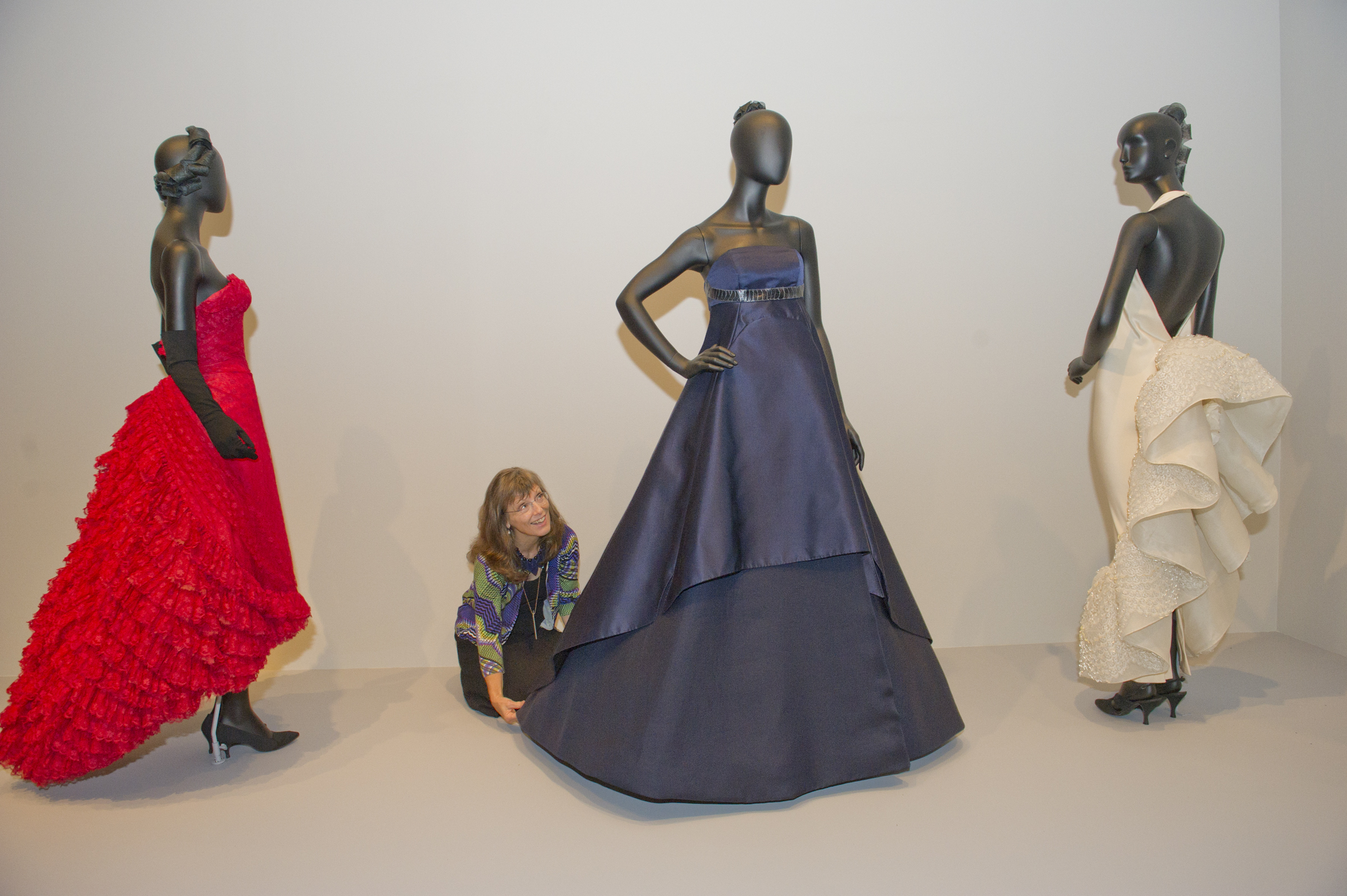 Curator Kristina Haugland fluffs up dresses, part of a new exhibit at the Philadelphia Museum of Art Dorrance Special Exhibition Galleries, October 5, 2018. The dresses are (L to R) A red lace evening gown by Jean DessŽs, circa 1958-59, A Ralph Rucci sting ray swan evening dress, circa, 2007, and a Pierre Cardin bustle back halter dress, circa 1990. Avi Steinhardt / For the Inquirer