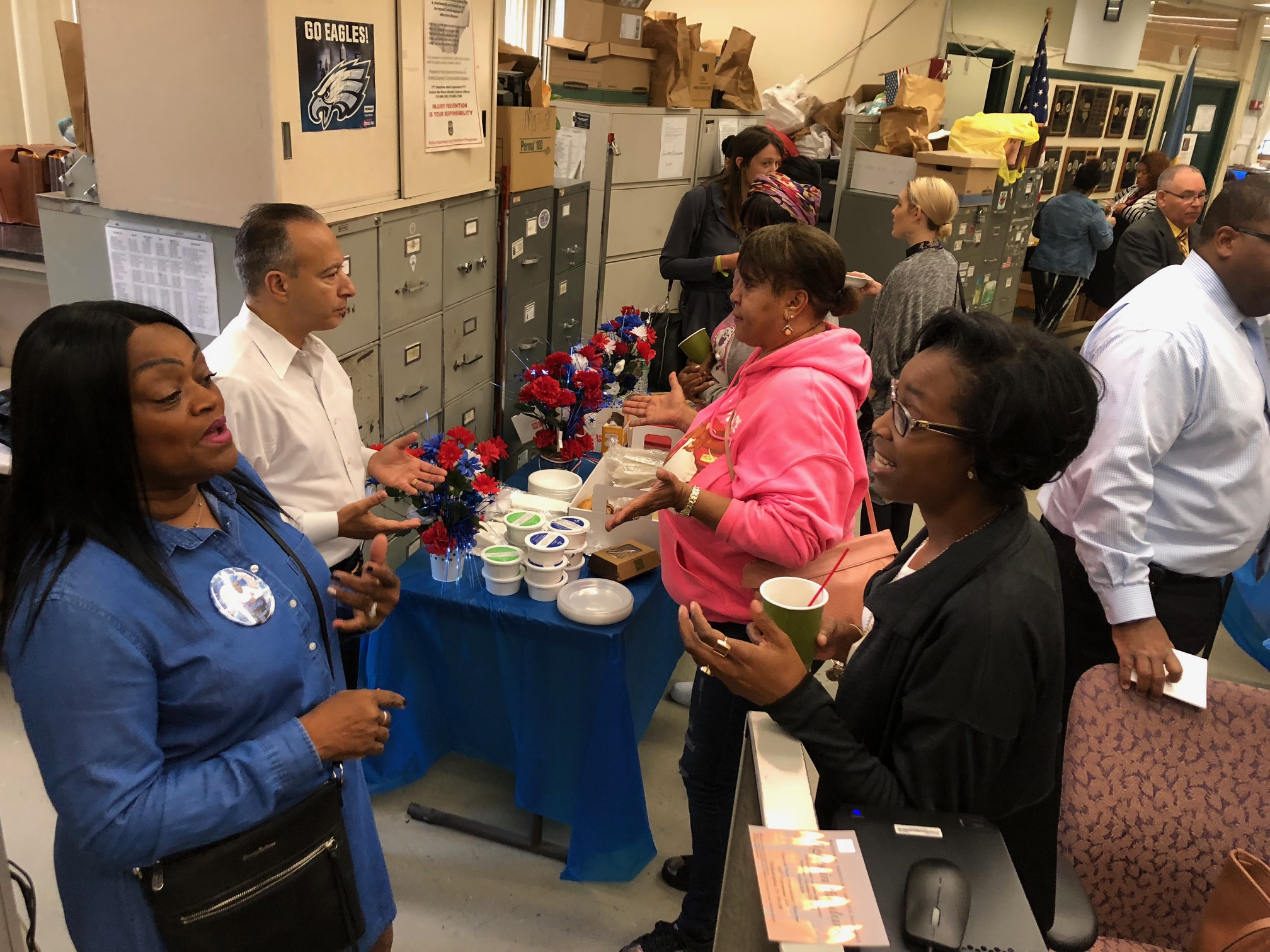 At a recent breakfast at Philadelphia´s homicide unit, detectives and loved ones of homicide victims gathered to meet and bond over coffee and bagels. Pictured in the blue shirt is Yullio Robbins whose son was killed in 2016 and behind her, the detective working on the case Gregory Santamala.