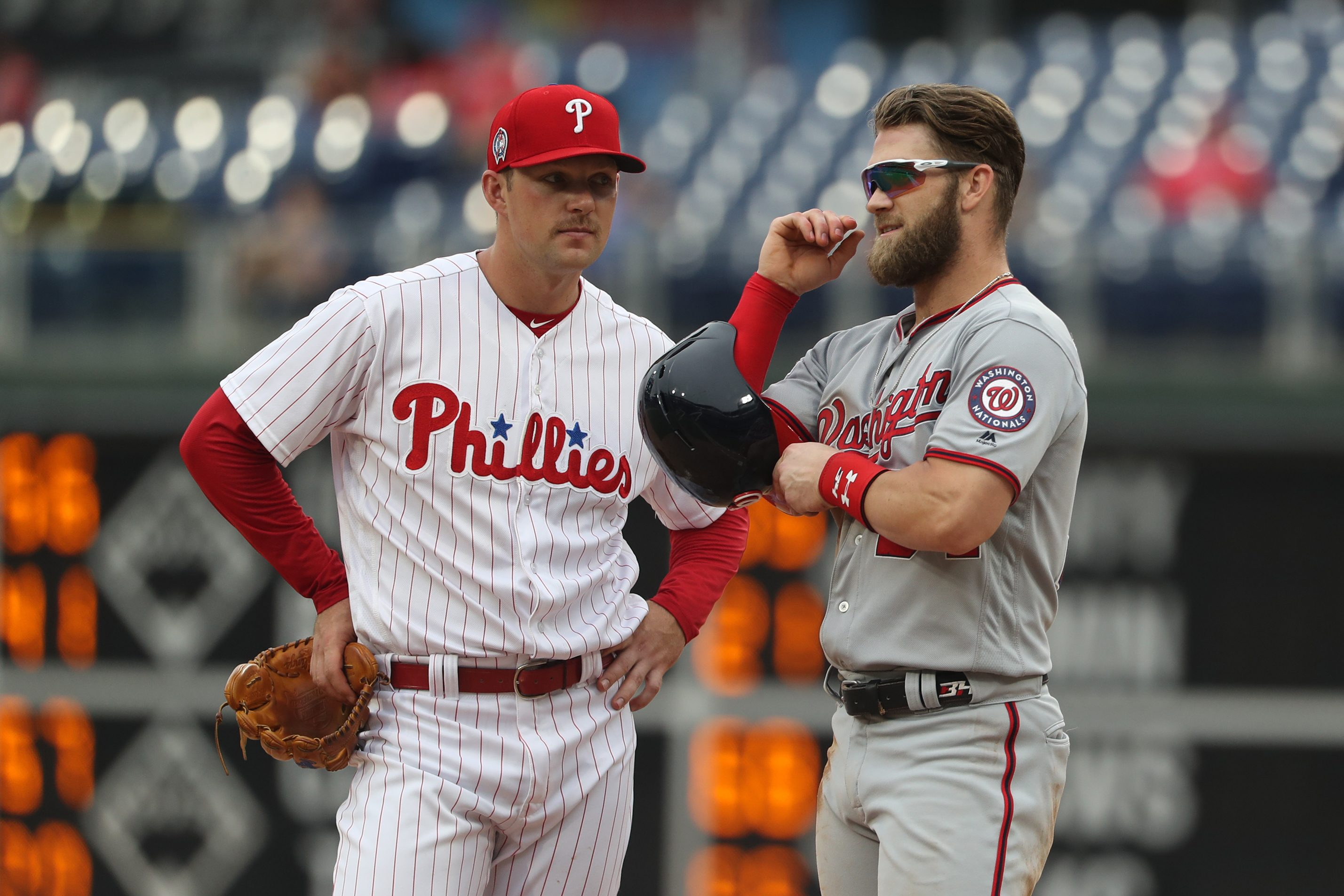 Rhys Hoskins (left) and Bryce Harper chat during a replay during a game on Sept. 11 vs. the Nationals on Sept. 11.