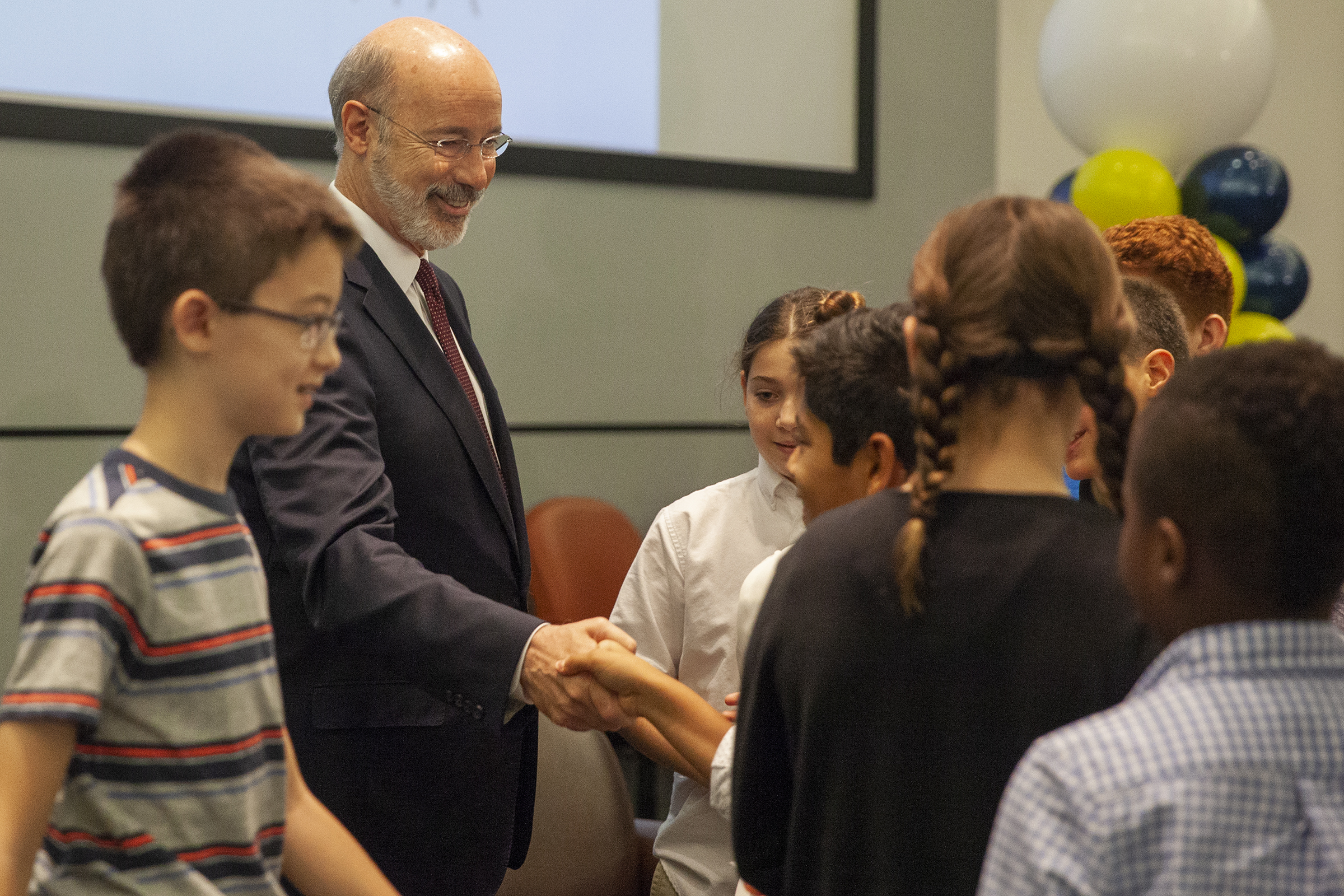 Gov. Wolf shakes hands with school children at the Philadelphia School District headquarters Oct. 10.