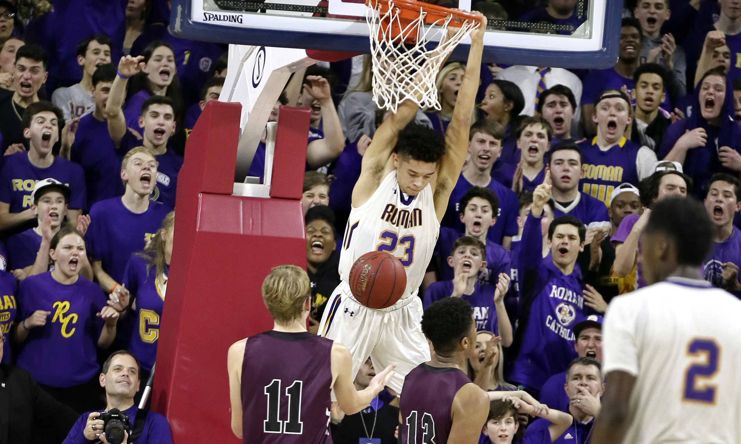 Roman Catholics Seth Lundy 23) hangs on the rim after his dunk against St. Josephs Prep in last seasons Catholic League semifinal. The Cahillites won, 69-66.