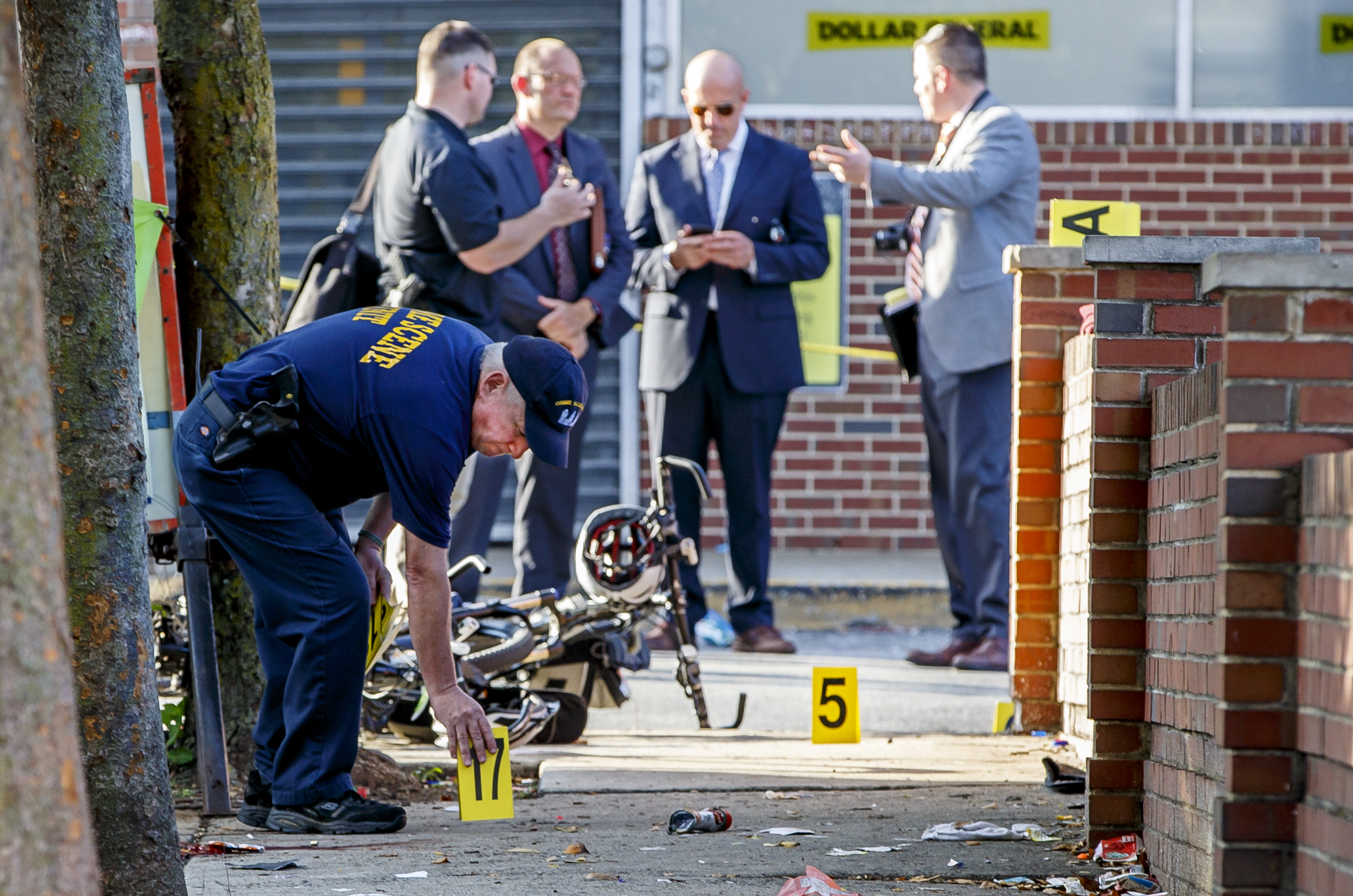 A member of the Philadelphia Police Crime Scene Investigation unit places a number where he has found another shell casing at the crime scene at Germantown Avenue where five people were shot by a single assailant who fled by automible, on October 3, 2018.
