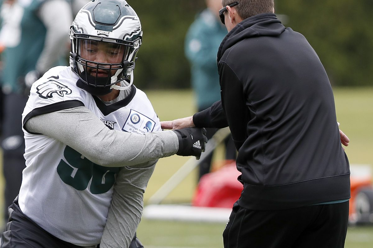 The Eagles' Derek Barnett (left) works with coach Dave Fipp during rookie camp.