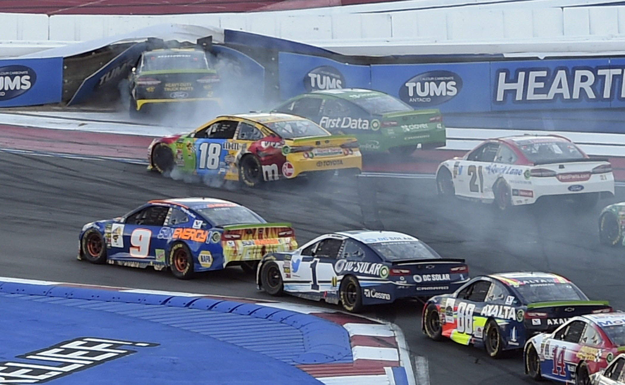Brad Keselowski (2) runs into the tire wall in Turn 1 as Kyle Larson (42), Kyle Busch (18) and Paul Menard (21) follow during the NASCAR Cup series auto race at Charlotte Motor Speedway in Concord, N.C., Sunday, Sept. 30, 2018. (AP Photo/Mike McCarn)