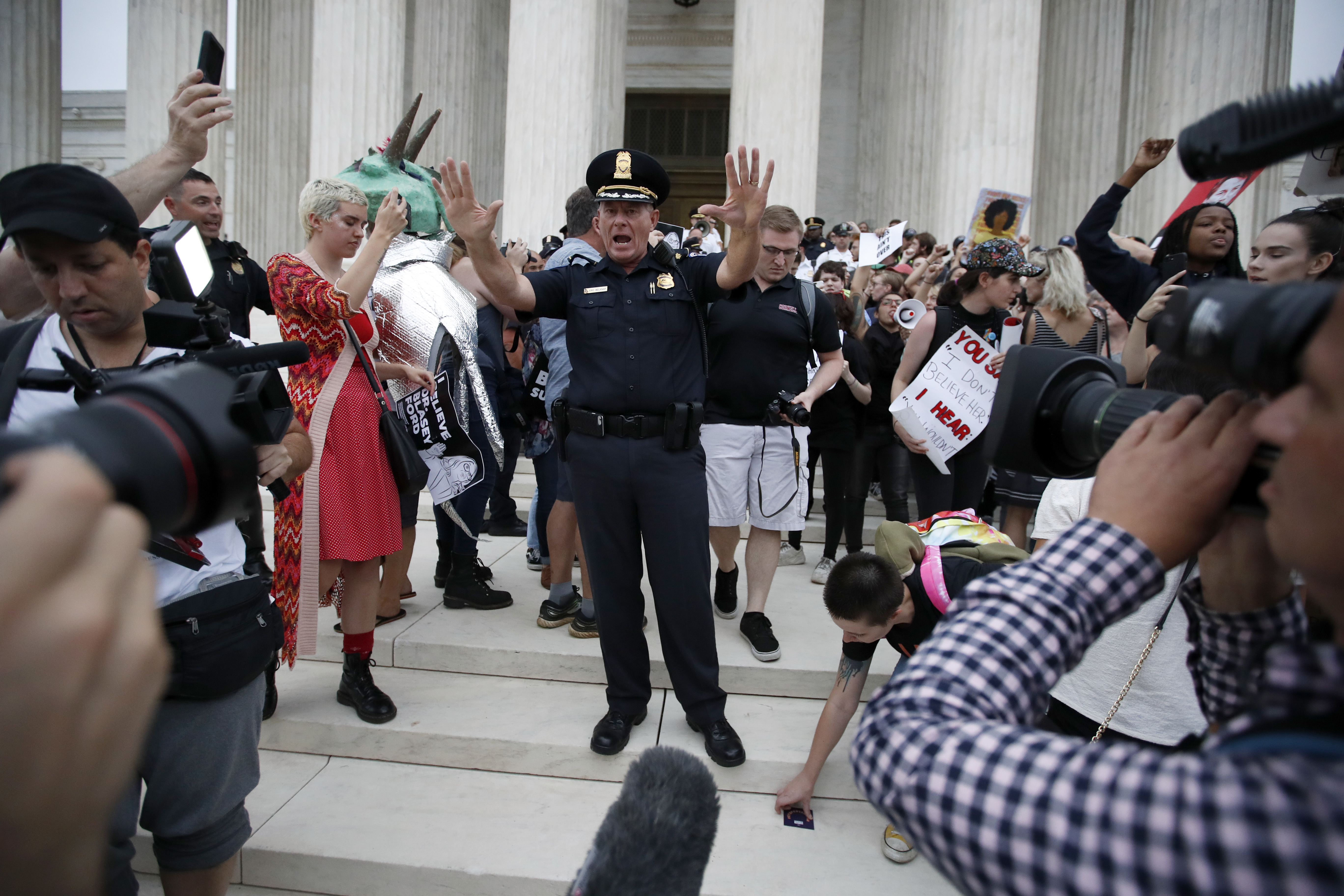 Police move activists as they protest on the steps of the Supreme Court after the confirmation vote of Supreme Court nominee Brett Kavanaugh, on Capitol Hill, Saturday, Oct. 6, 2018 in Washington.