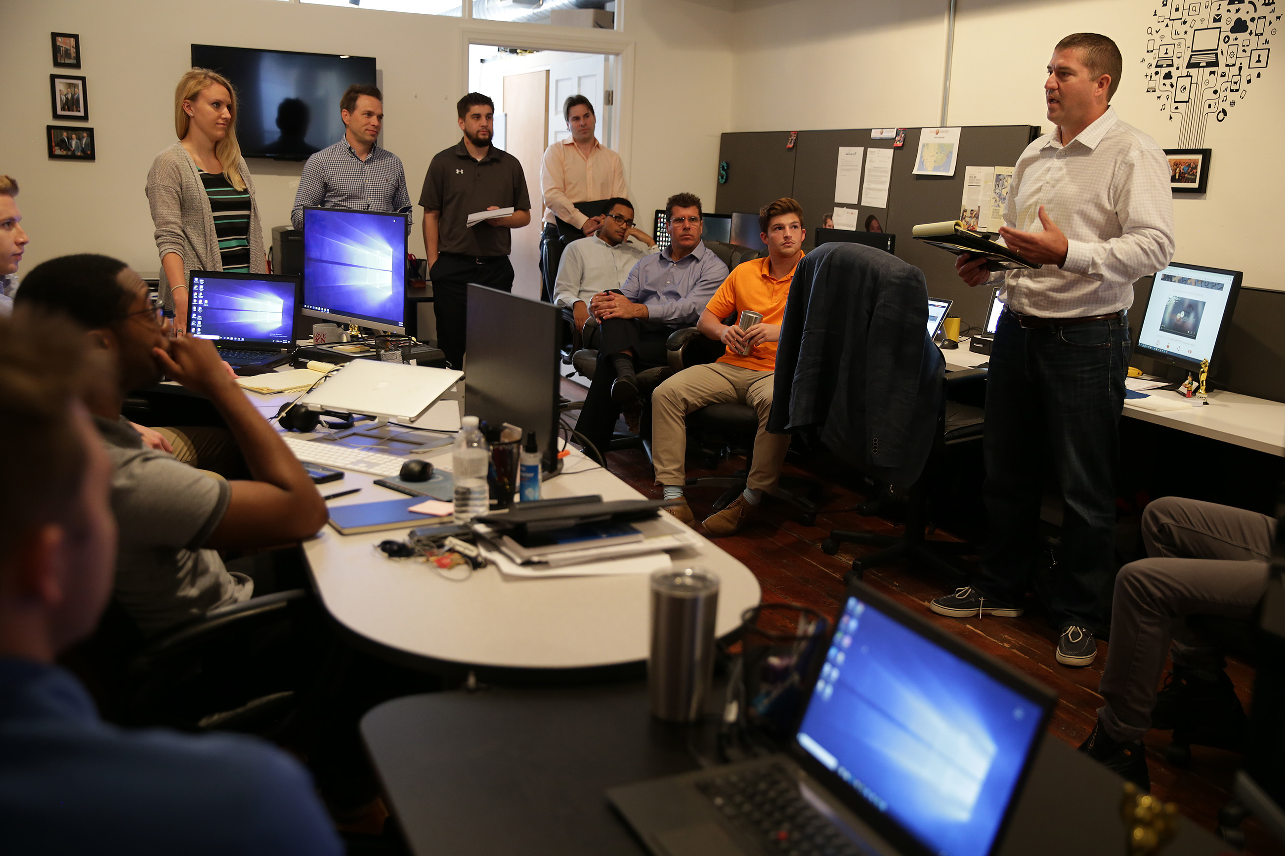 """Scott Catron, (right) cofounder of Social Detection, leads the """"daily huddle"""" at their office in Old City, one of the ways in which the start-up tries to build camaraderie among employees and, he hopes, retention."""