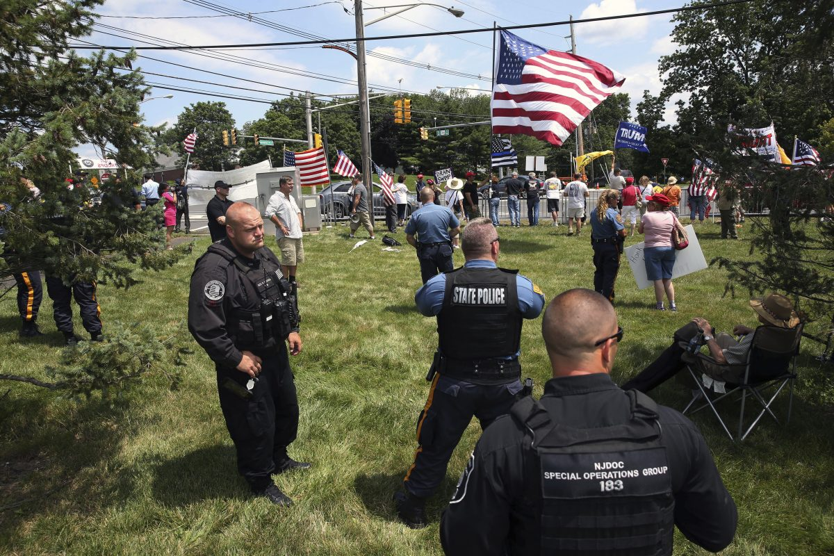 Police officers stand near as groups of President Donald Trump supporters and protesters wave flags and signs at passing motorists during gatherings not far from Trump National golf course, where Trump was attending the Women's US Open tournament, Saturday.