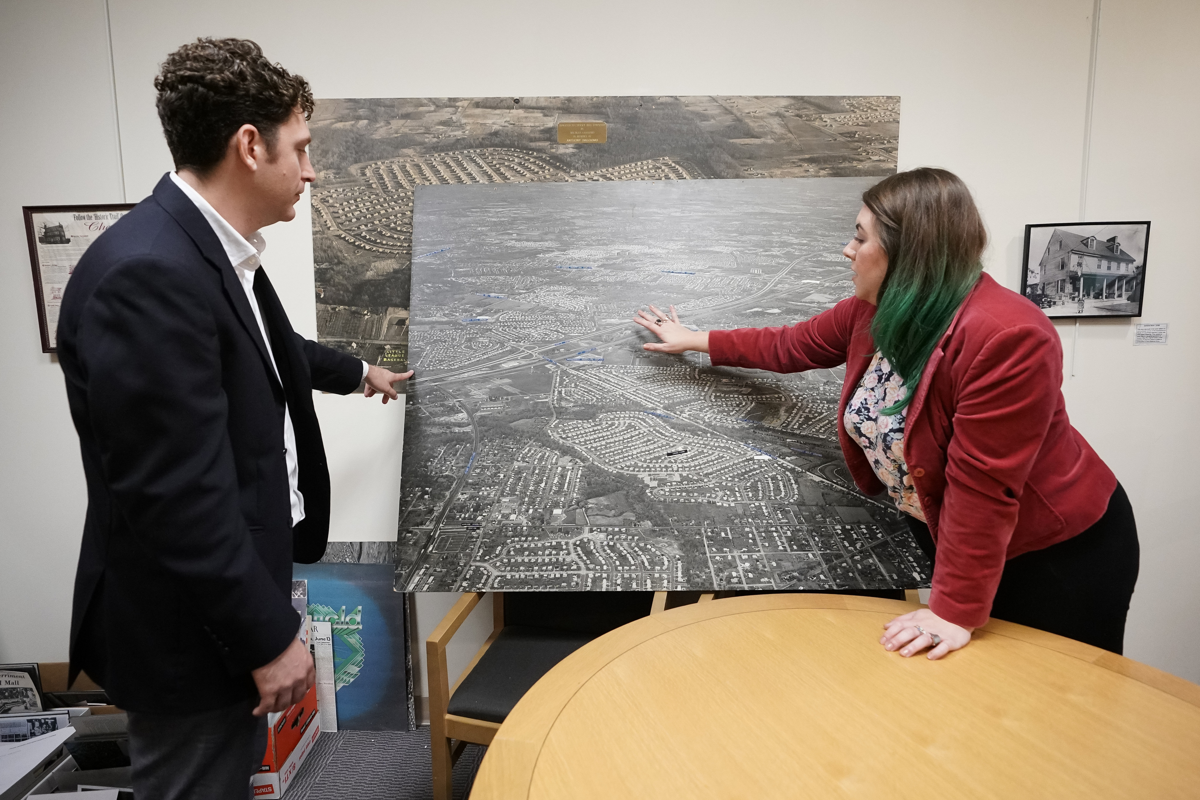 Adam Tecza, left, of Group Melvin Design, and Lorissa Luciani, Cherry Hill´s director of community development, examine a vintage aerial map of the township´s Kingston neighborhood at the Cherry Hill Library. Kingston is among 16 neighborhoods the township´s new master plan cites as potentially in need of rehabilitation.